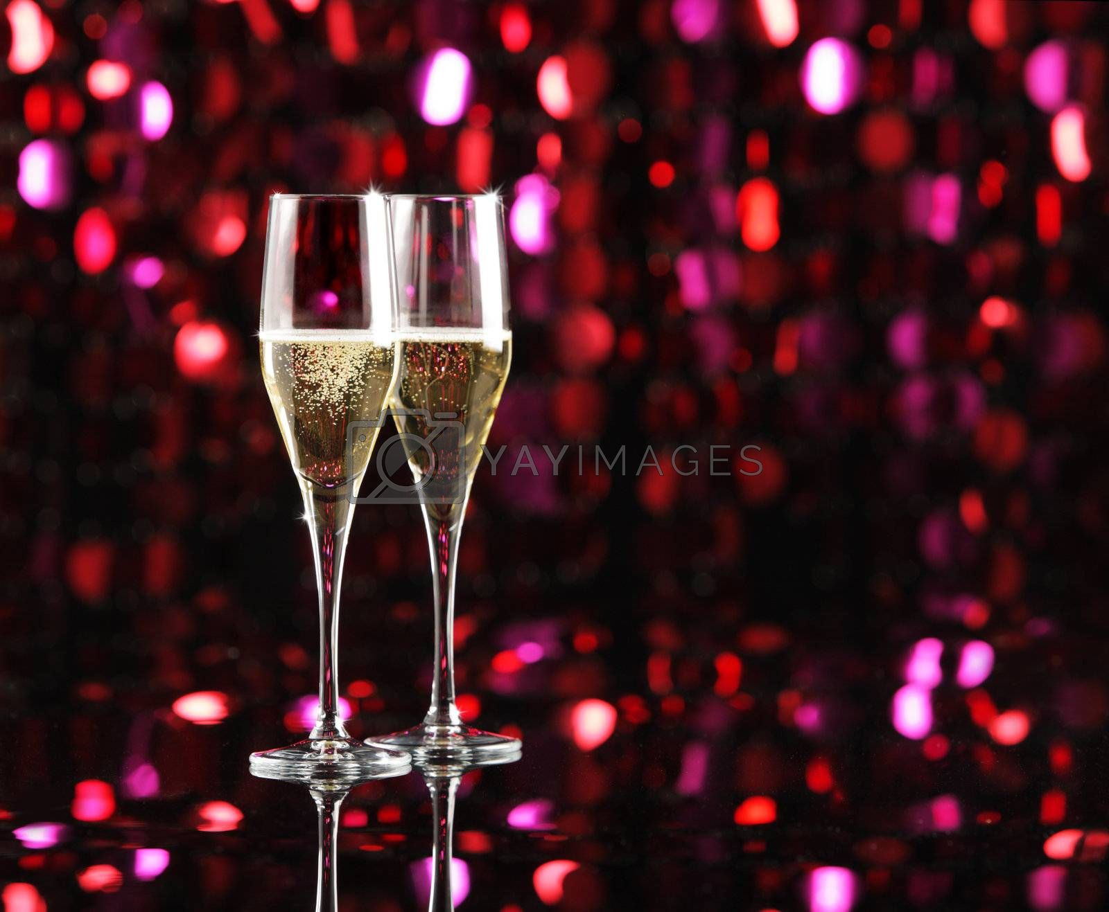 Two glasses of champagne, colored lights as background