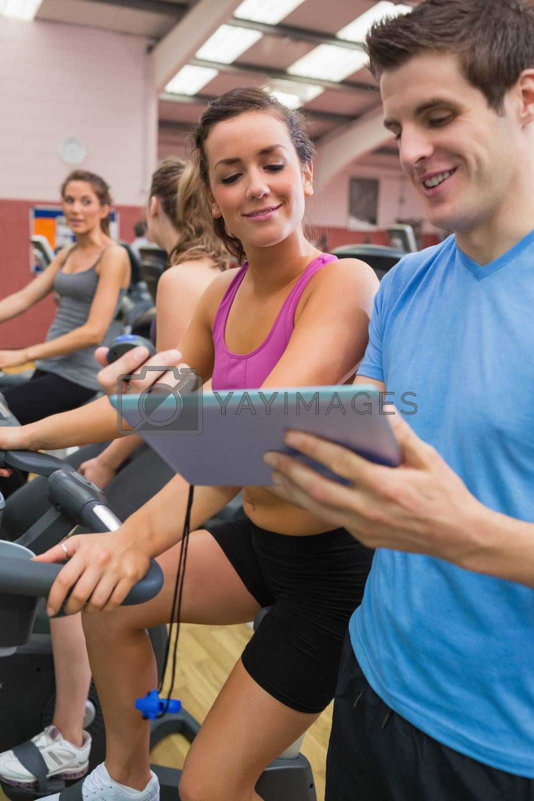 People chatting in gym on exercise bicycles