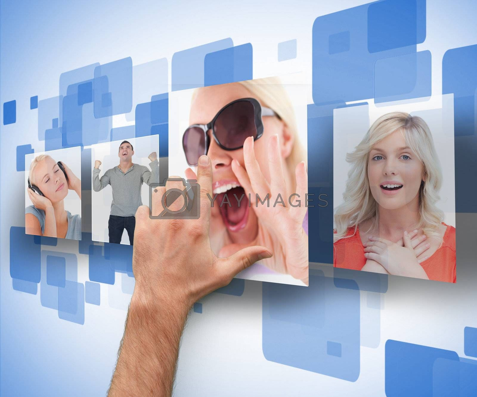 Male hand selecting one of four photos on digital blue wall