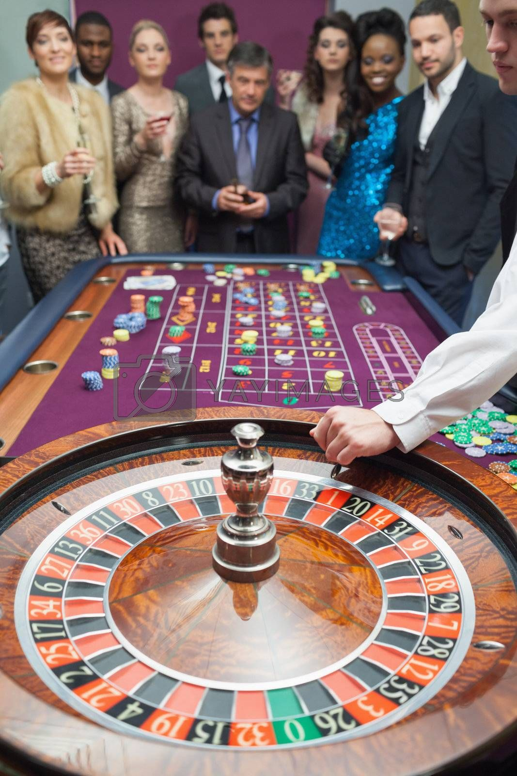 People standing at the roulette table in casino