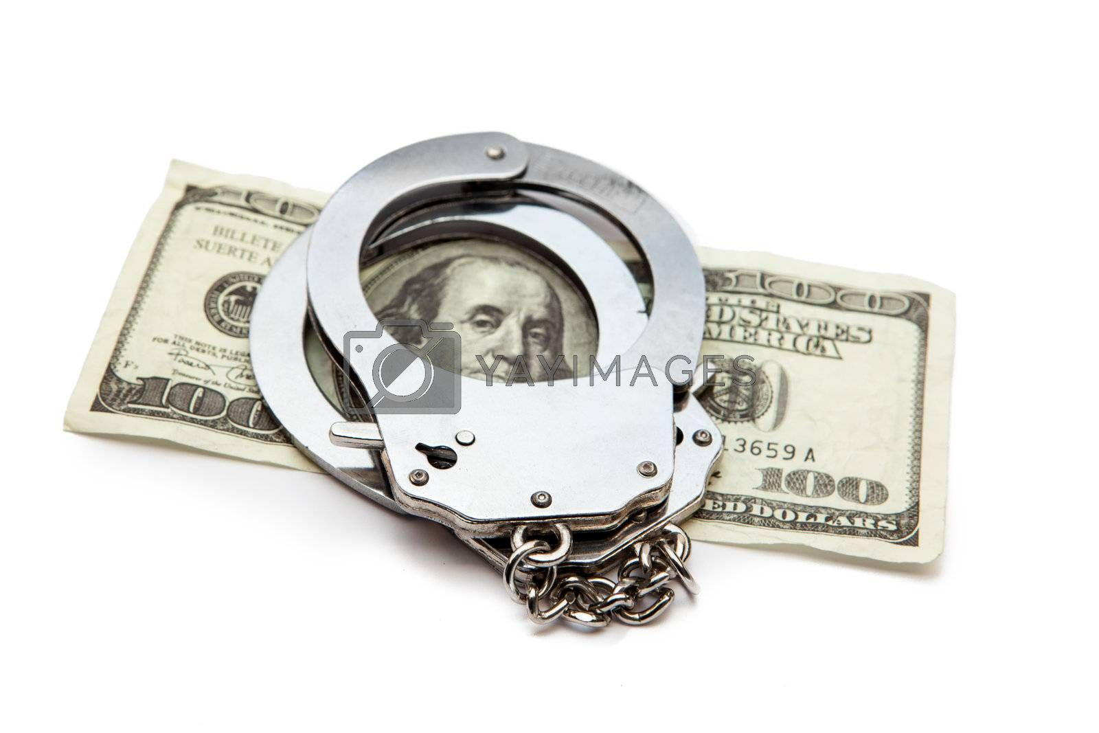 Money and handcuffs lying against white background