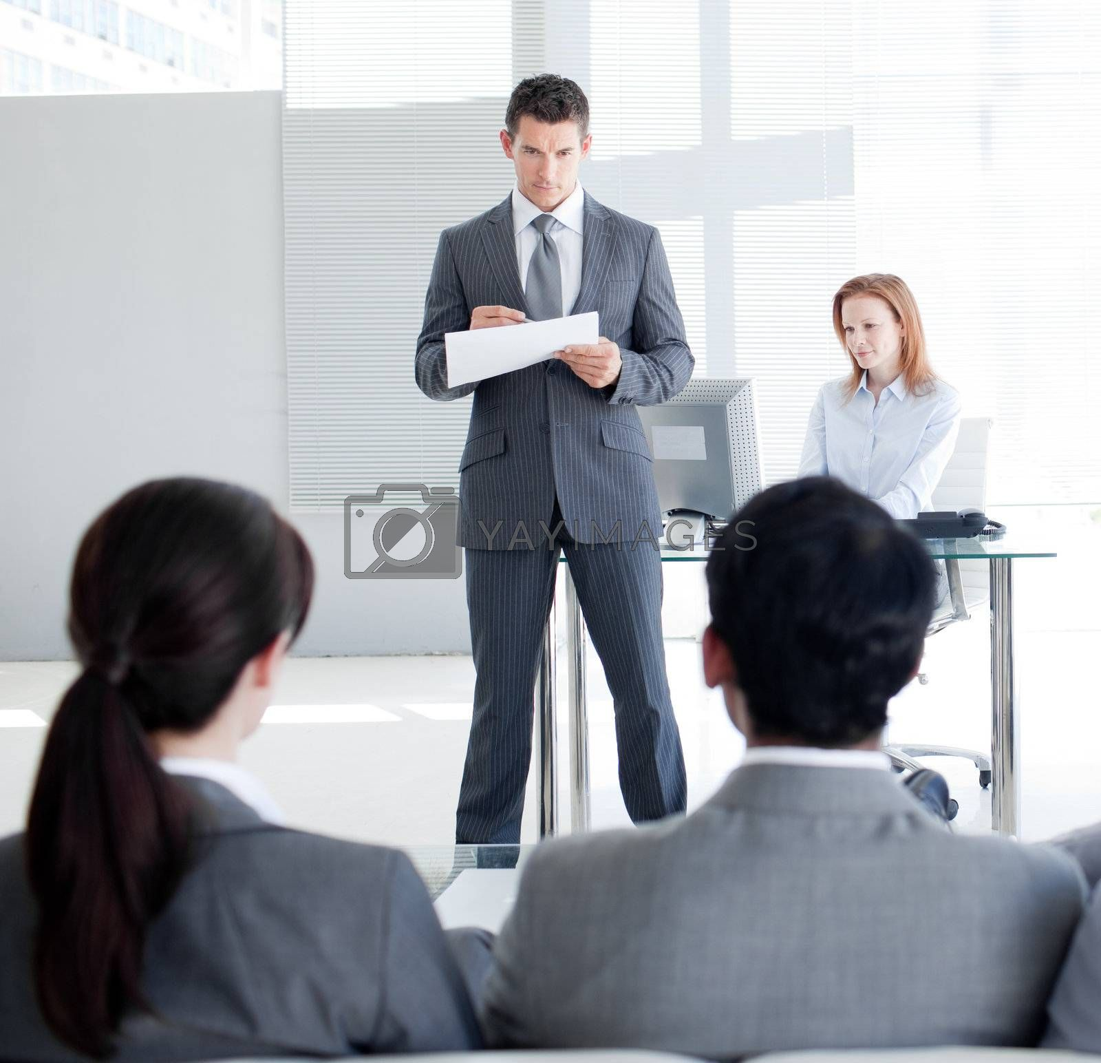 An attractive teamleader talking to his colleagues in an office