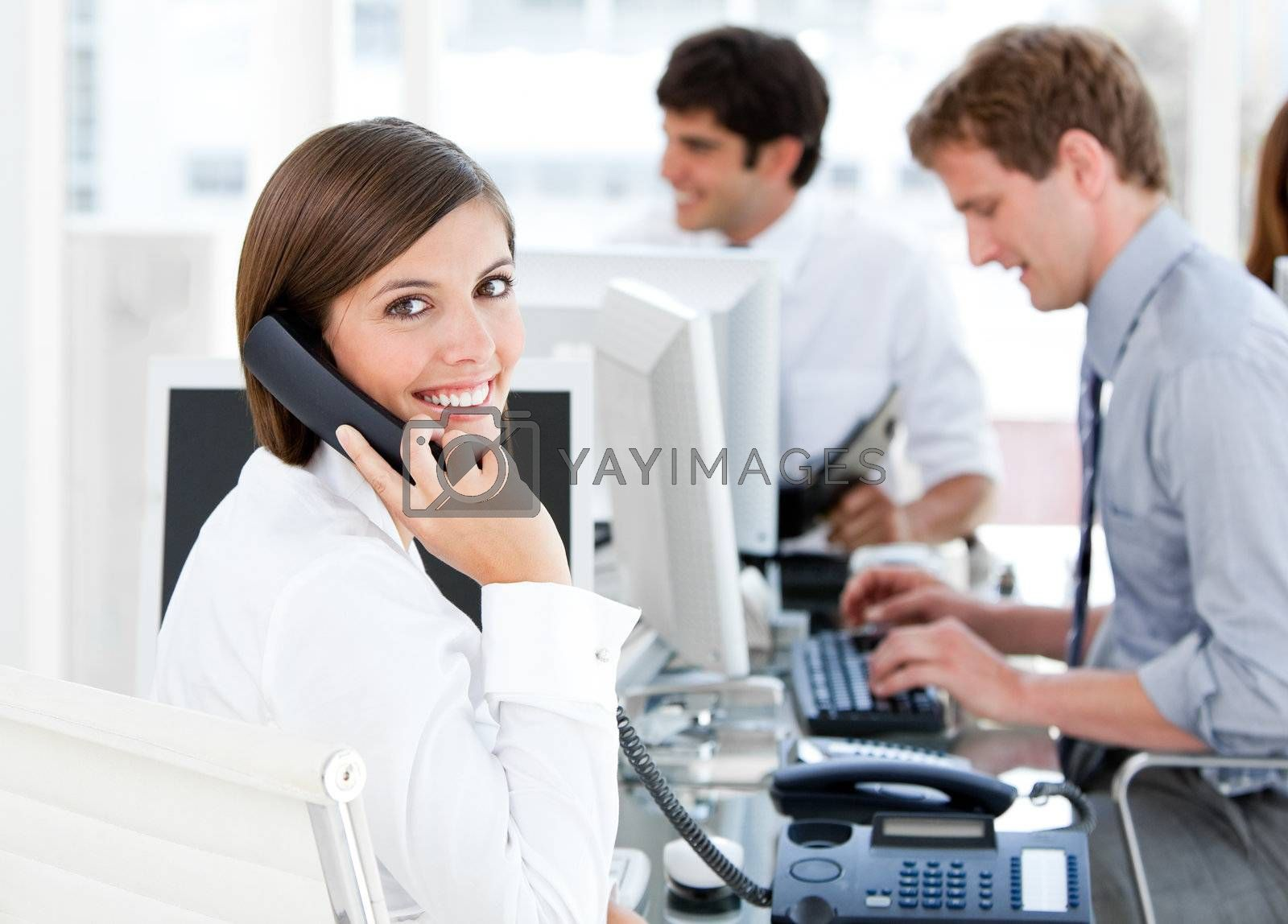 Smiling businesswoman talking to the phone in the open-space