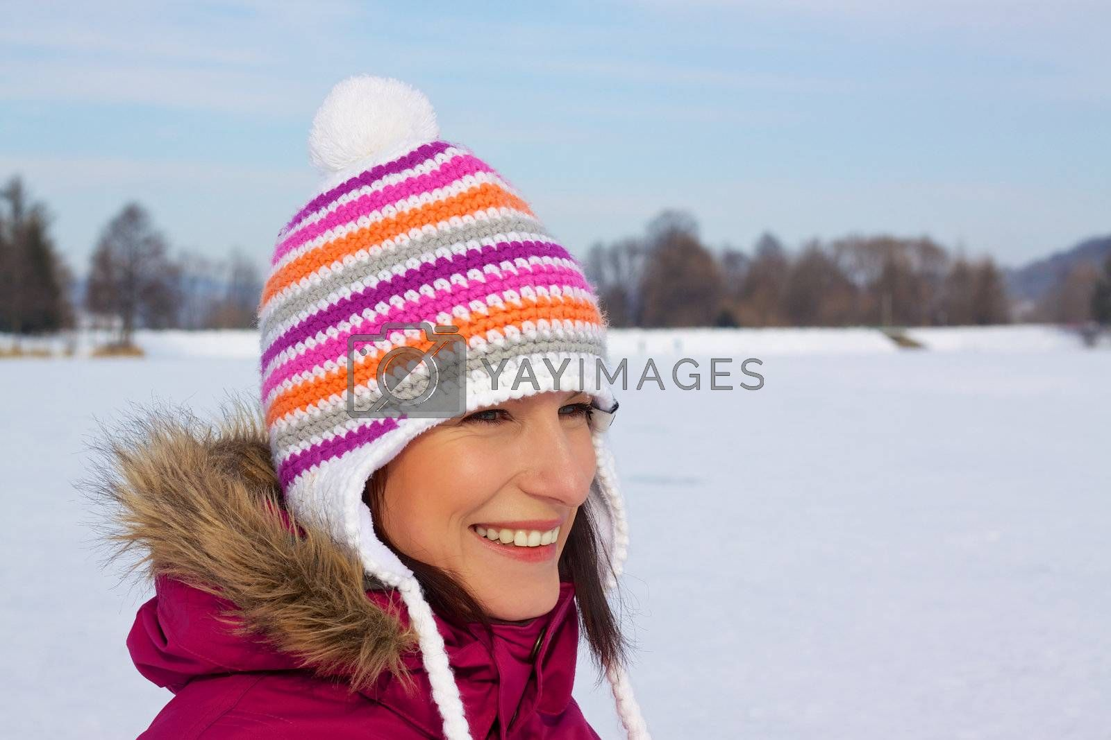 Smiling young woman wearing knitted winter cap with natural winter background