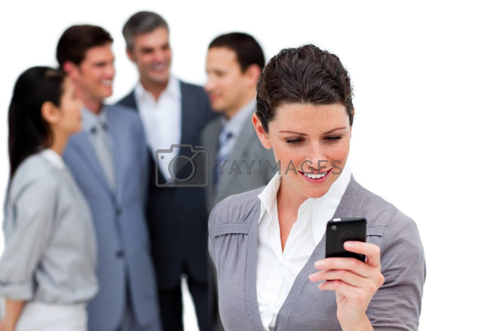 Attractive businesswoman looking at her cellphone in front of her team against a white background