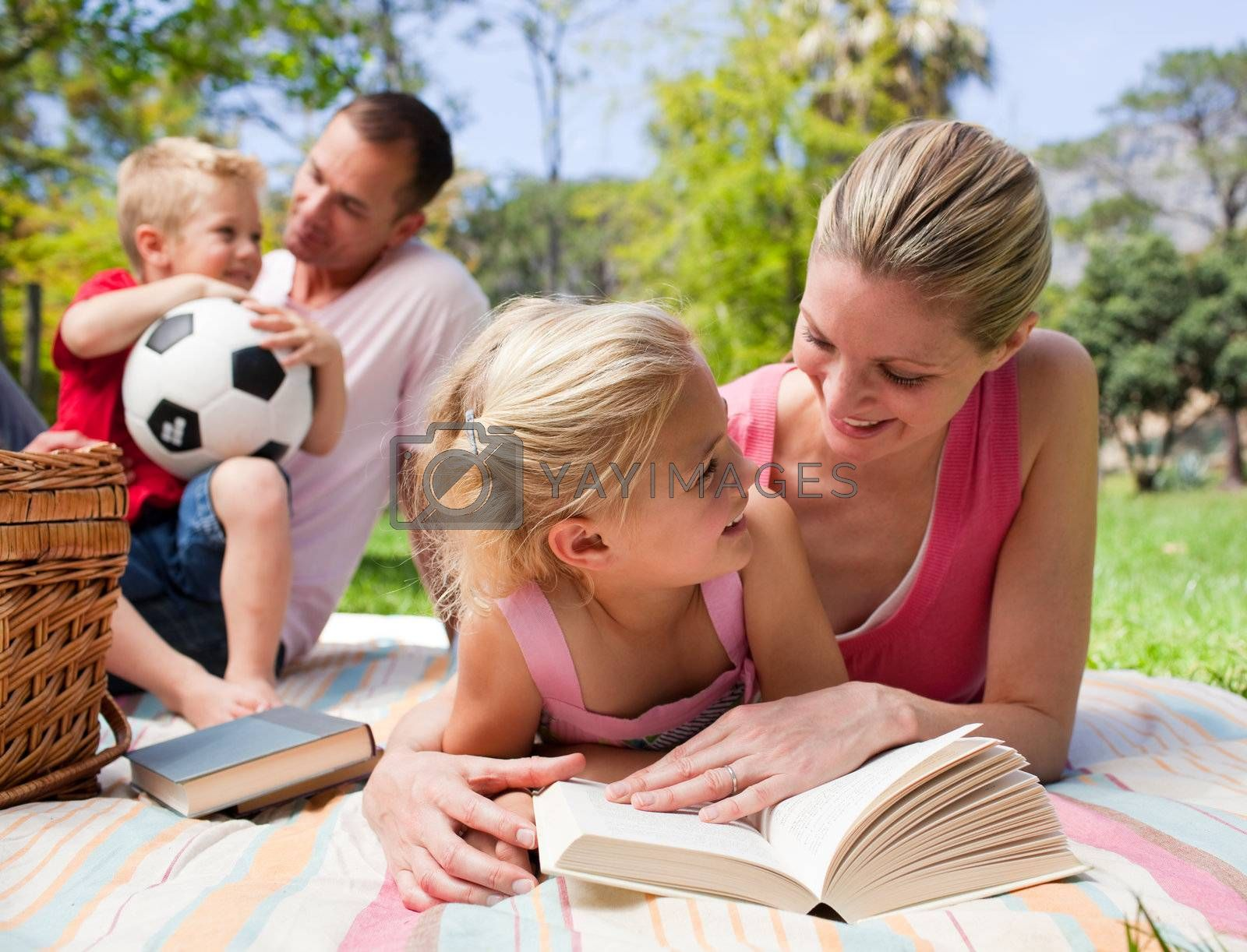 Mother and her daughter reading at a picnic with their family by Wavebreakmedia