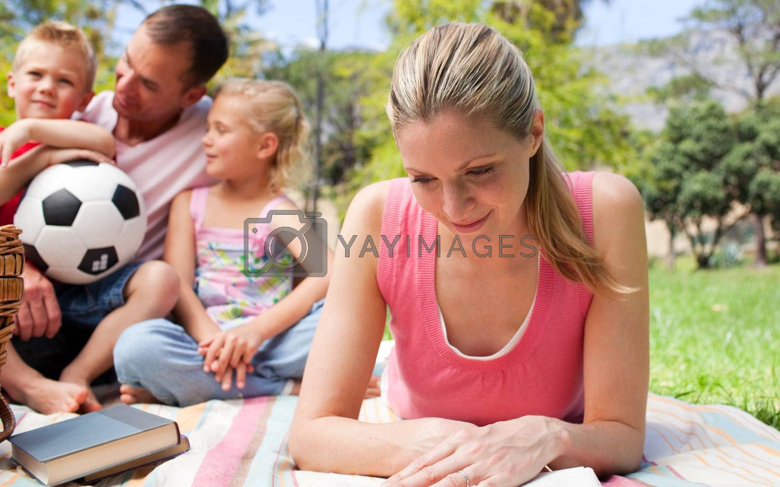 Concentrated mother reading at a picnic with her family in the background