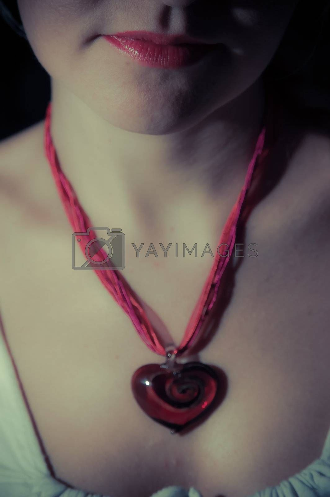 A girls lips with a red heart pendant