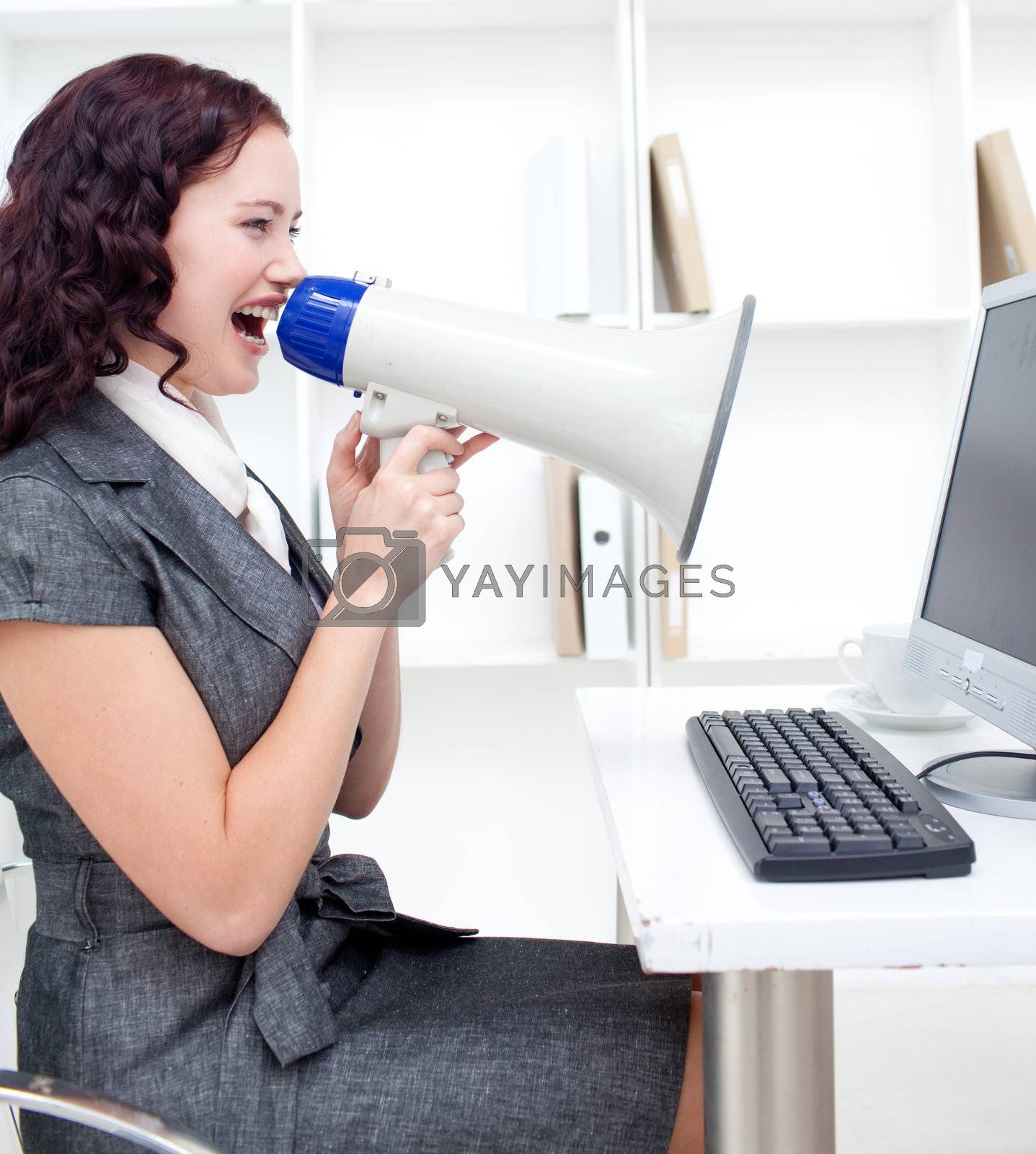 Businesswoman yelling through a megaphone in office