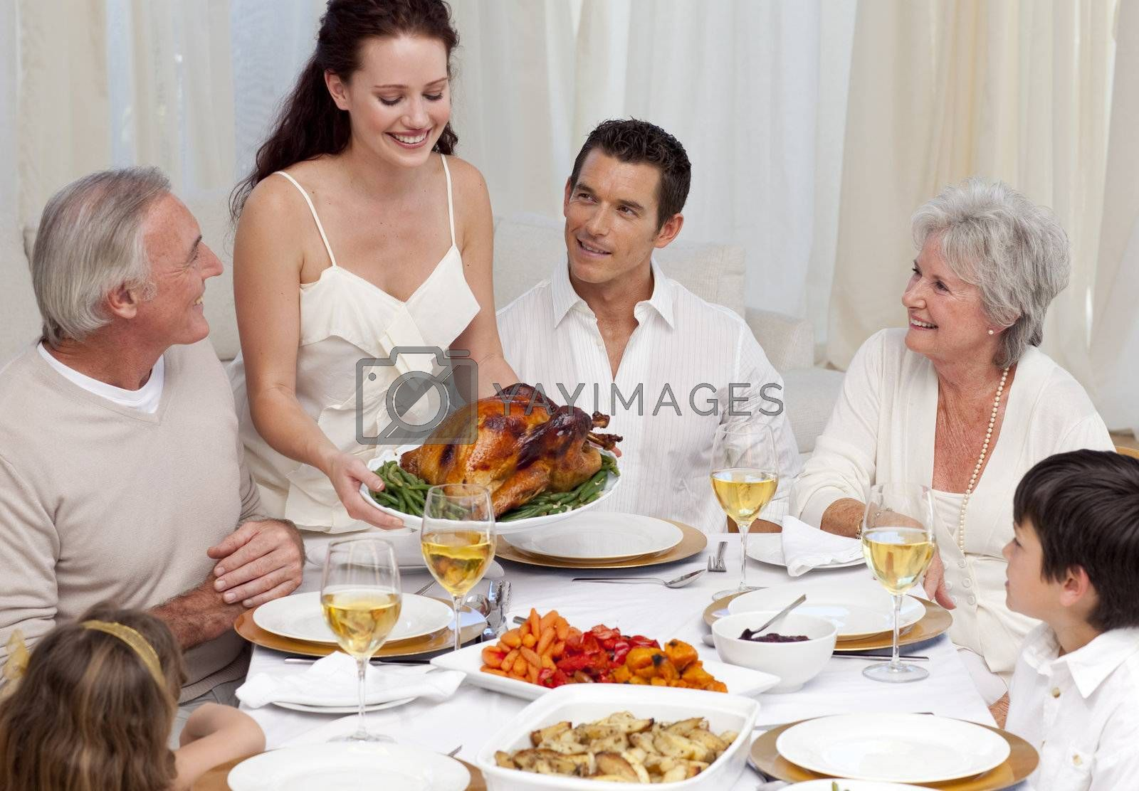 Woman showing turkey to her family for Christmas dinner at home