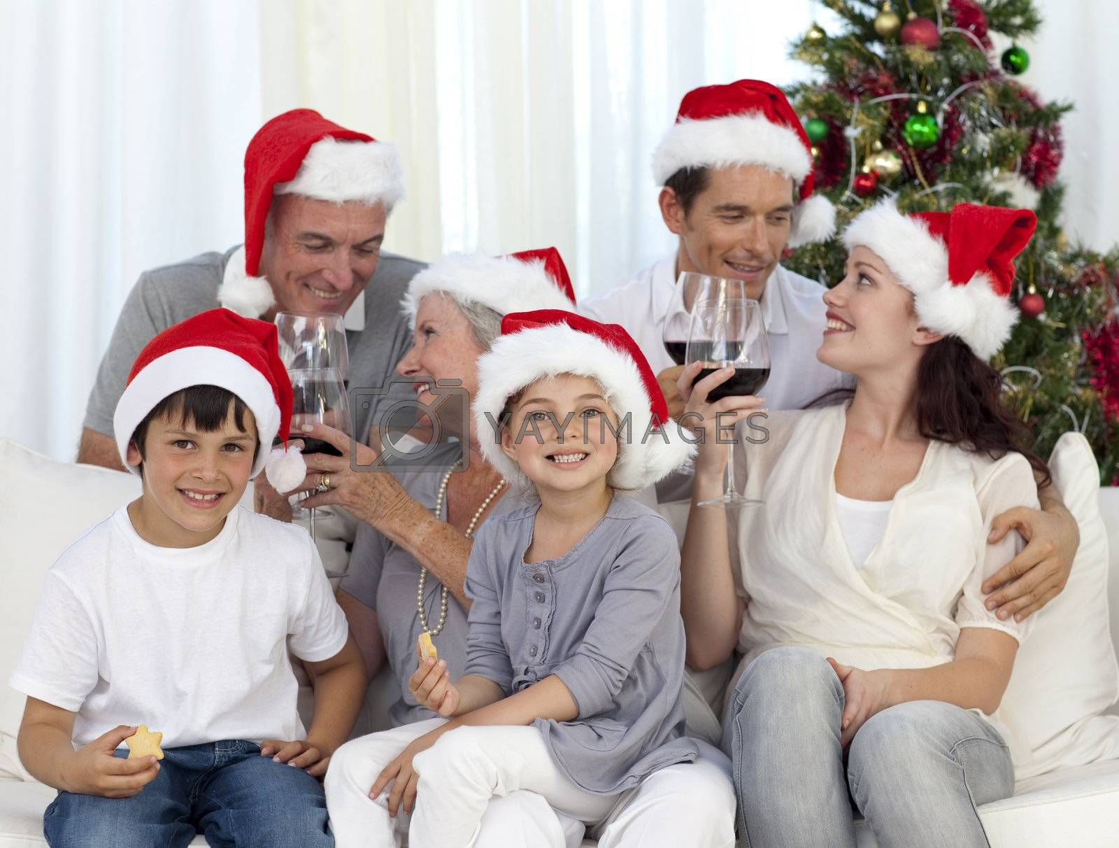 Family sitting on sofavcelebrating Christmas with wine and sweets