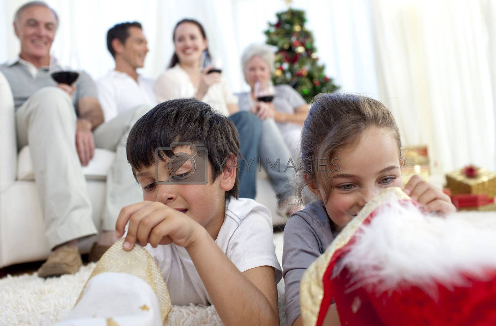 Children looking for presents in Christmas boots and family on sofa
