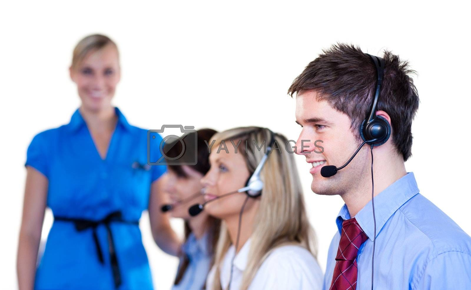 Businesspeople talking with headset in a call center businessmanager in background