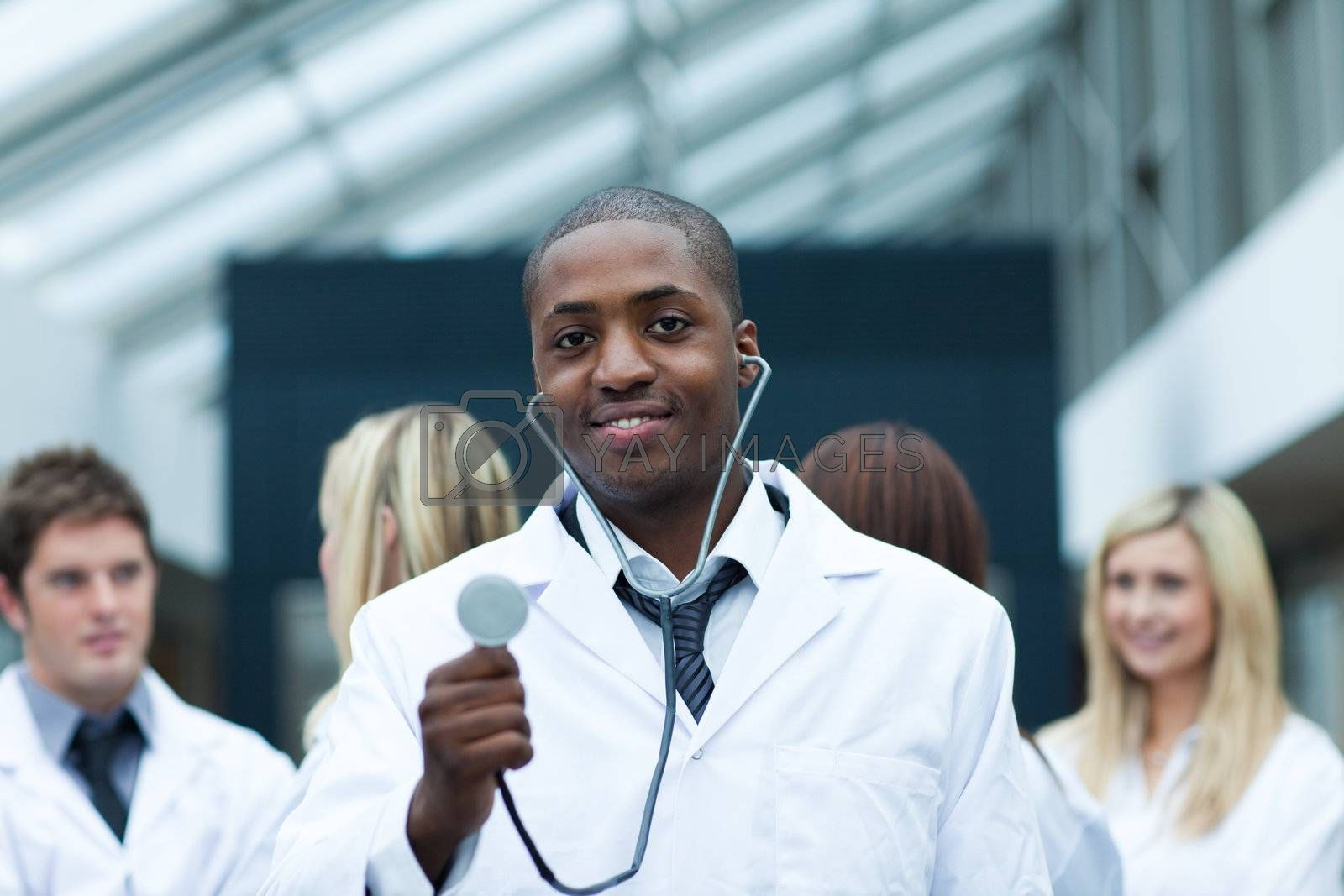 Ethnic doctor with his team in the background smiling at the camera