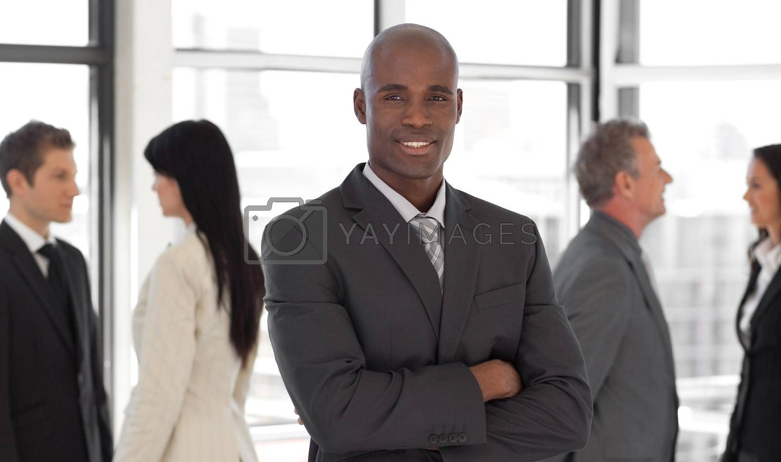Smiling ethnic business leader in front of team