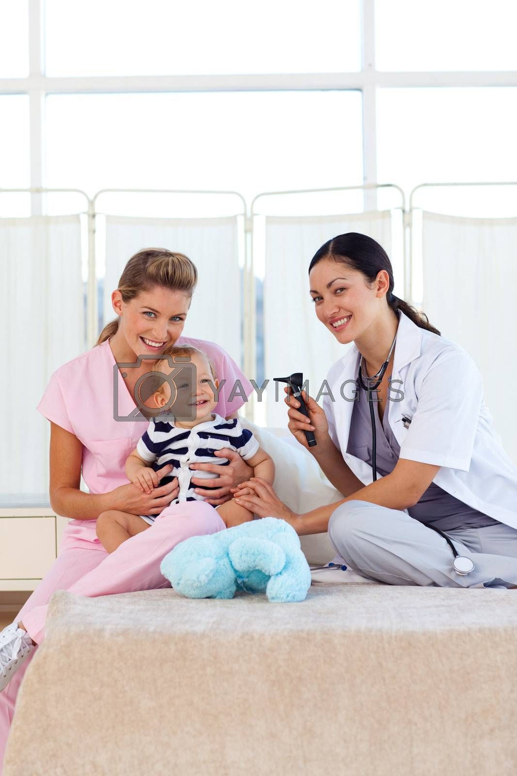 Baby with pediatrician and nurse in hospital with copy-space