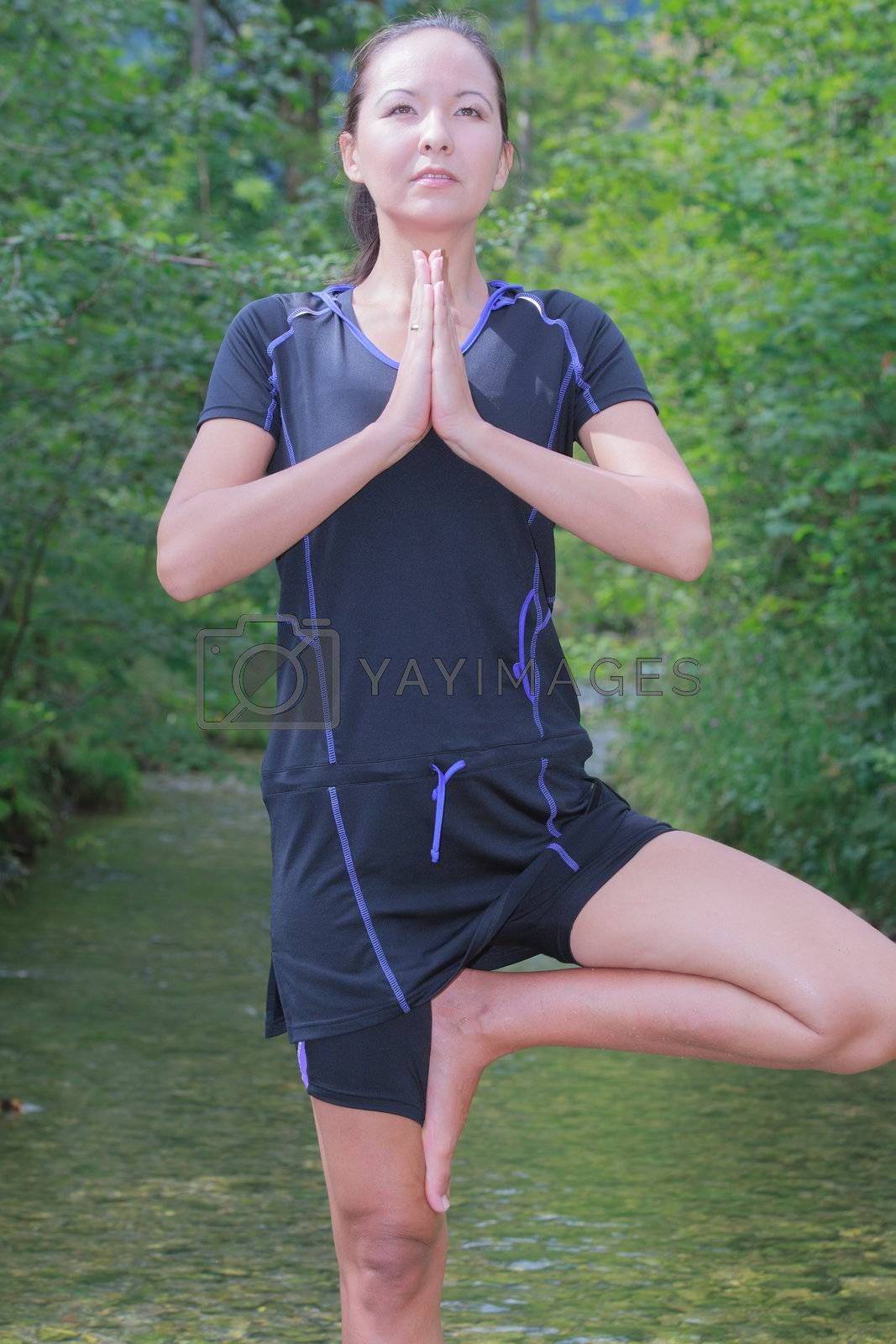 Woman doing yoga in the creek and standing on one foot