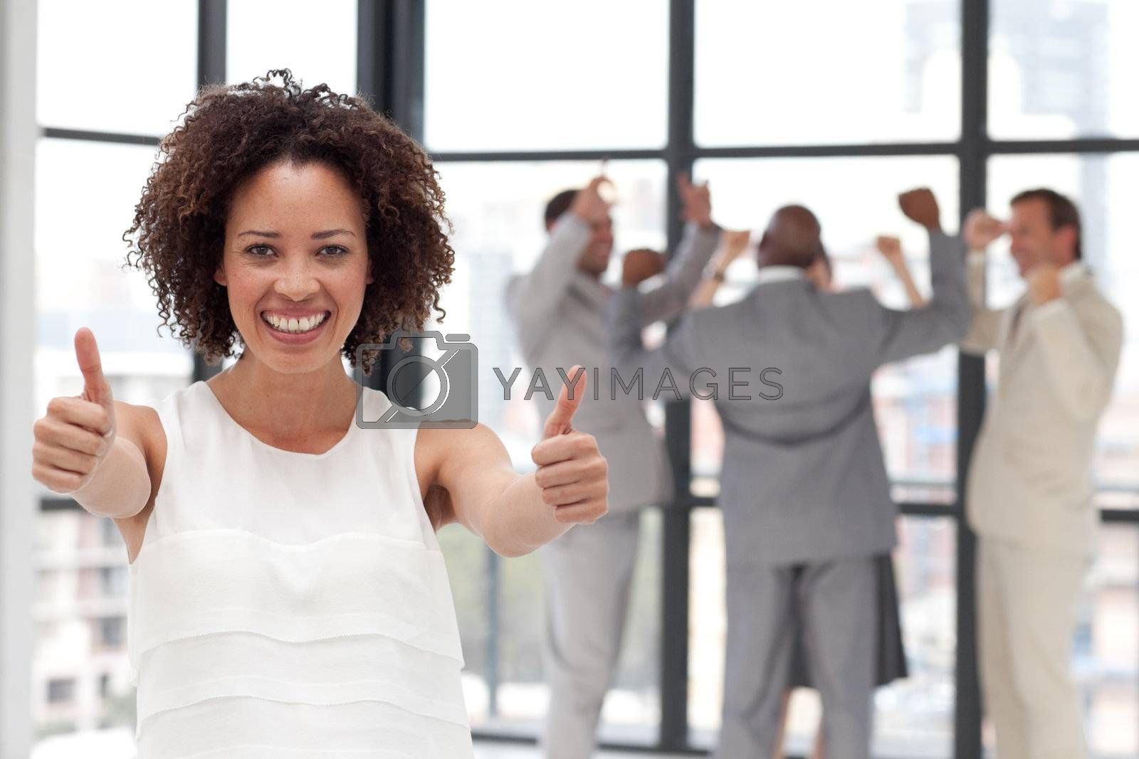 Successful Businesswoman doing a thum-up with his colleagues in the background