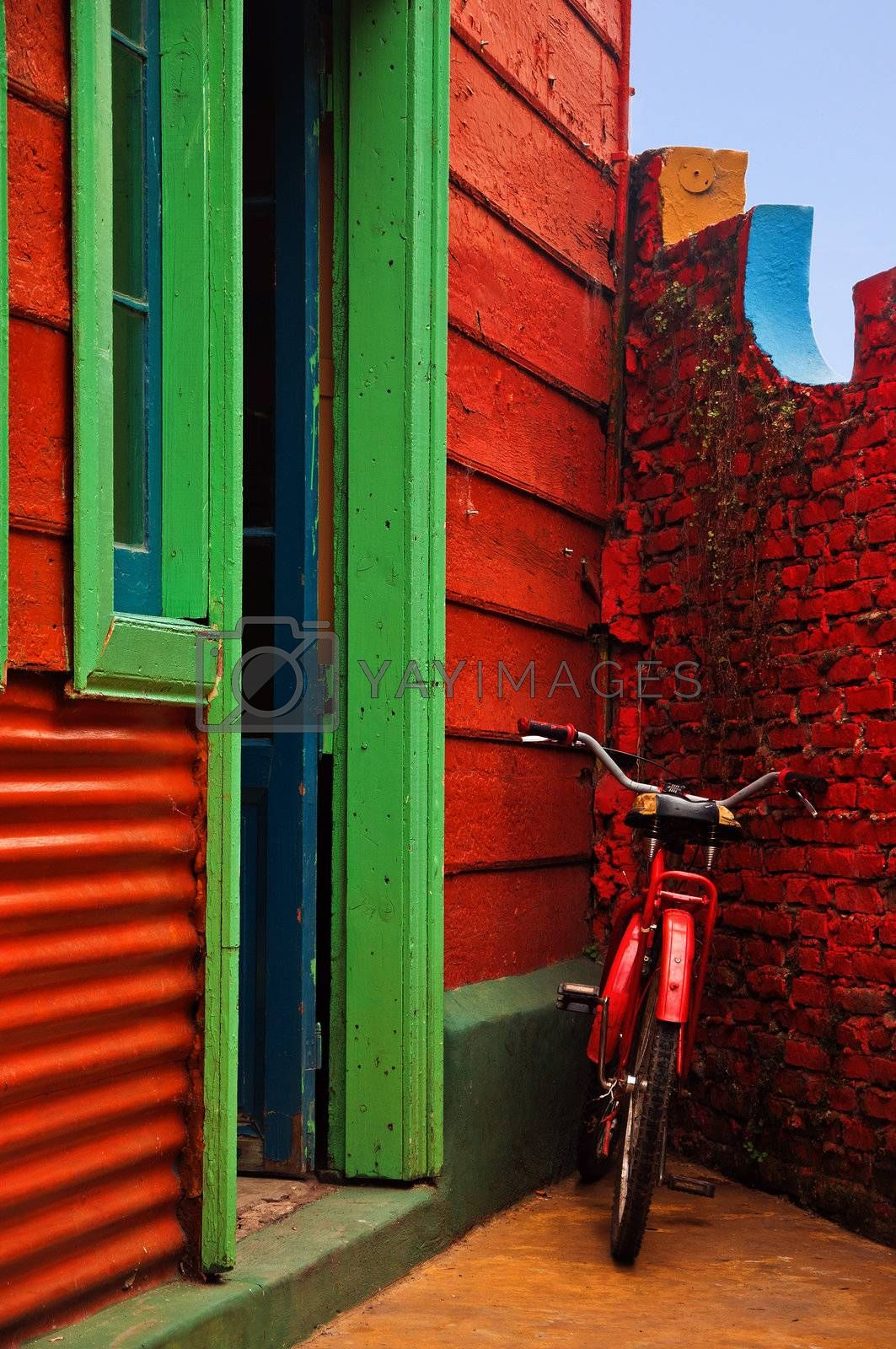 A red bicycle resting against a red wall in Buenos Aires, Argentina.