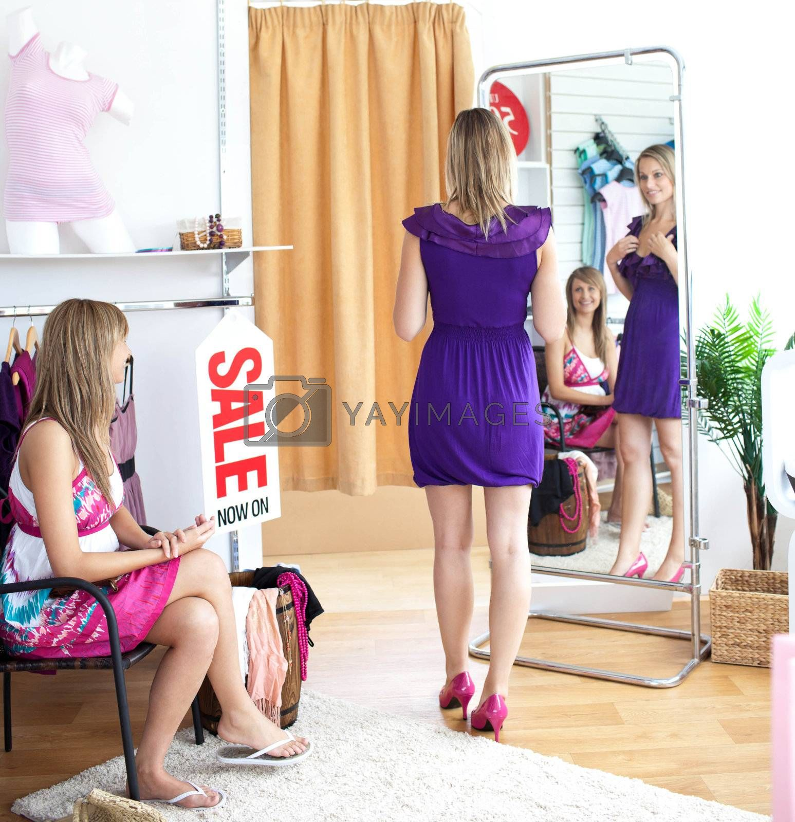 Cute women choosing clothes together in a shop