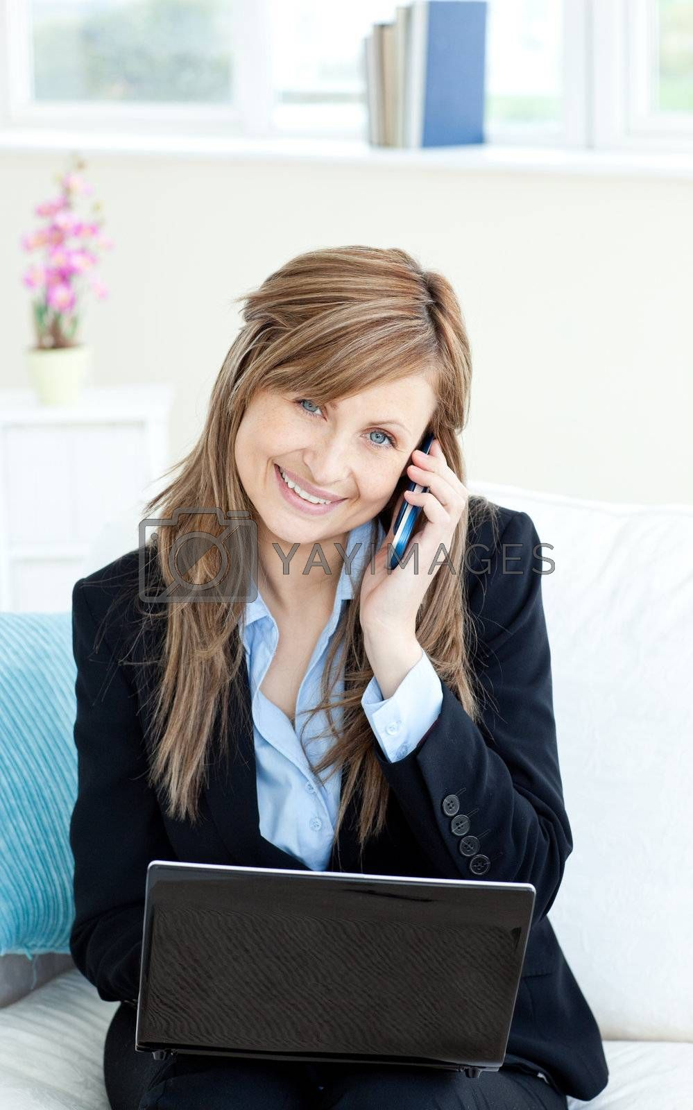 Beautiful confident businesswoman using a mobile phone and a laptop in the office