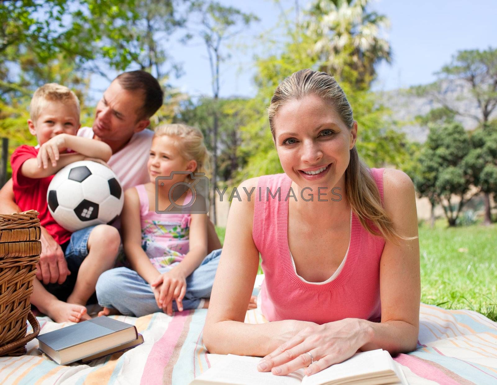 Smiling woman reading at a picnic with her family in the background
