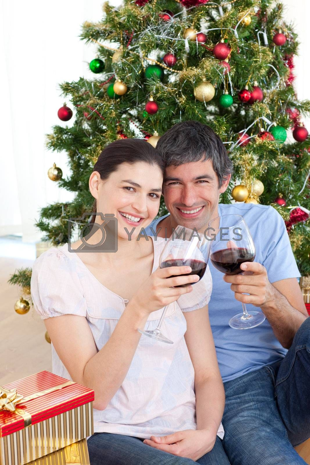 Happy couple drinking wine at homa at Christmas time
