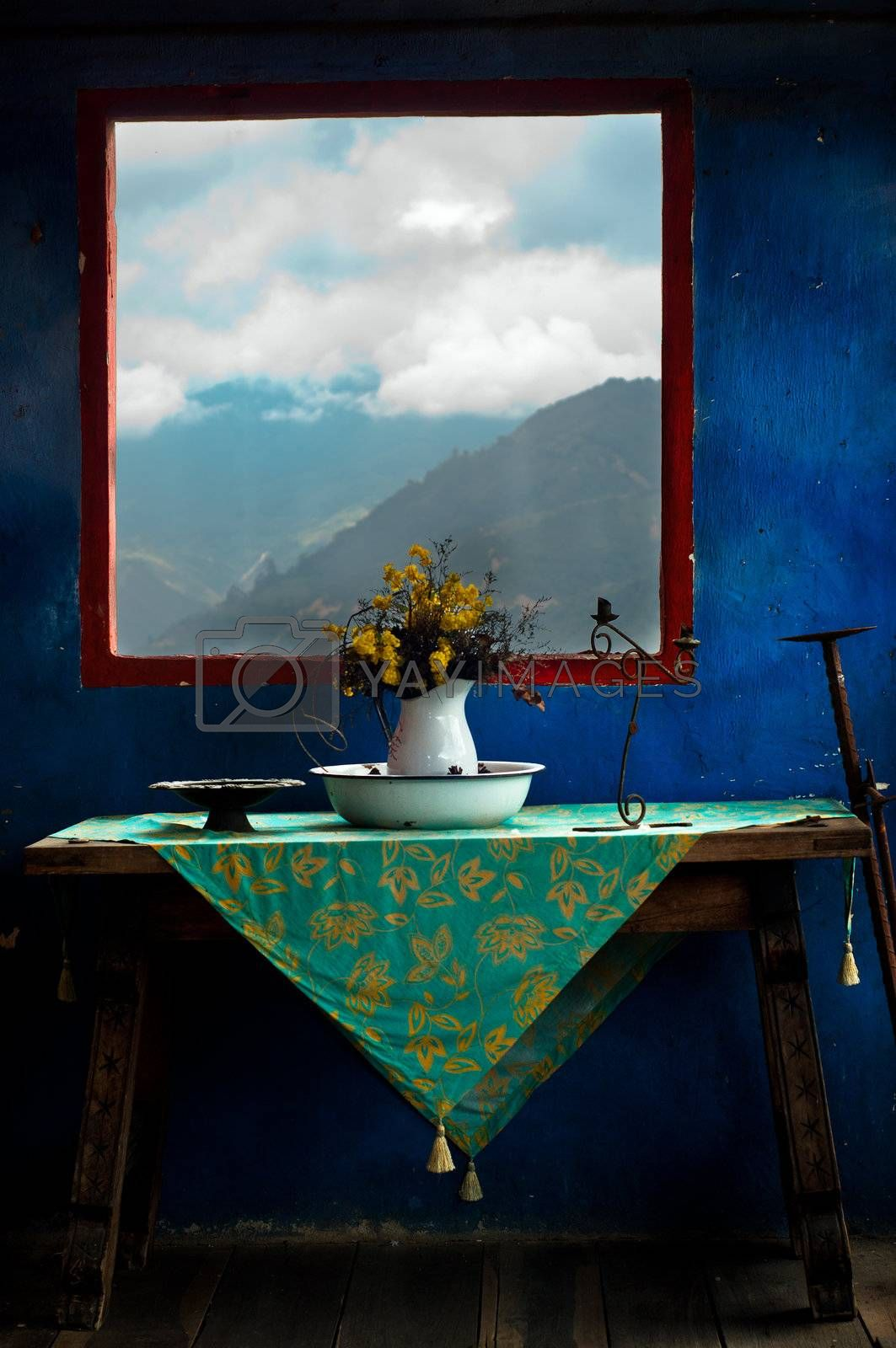 Flowers sitting on a table with a blue wall and a mountain behind them.
