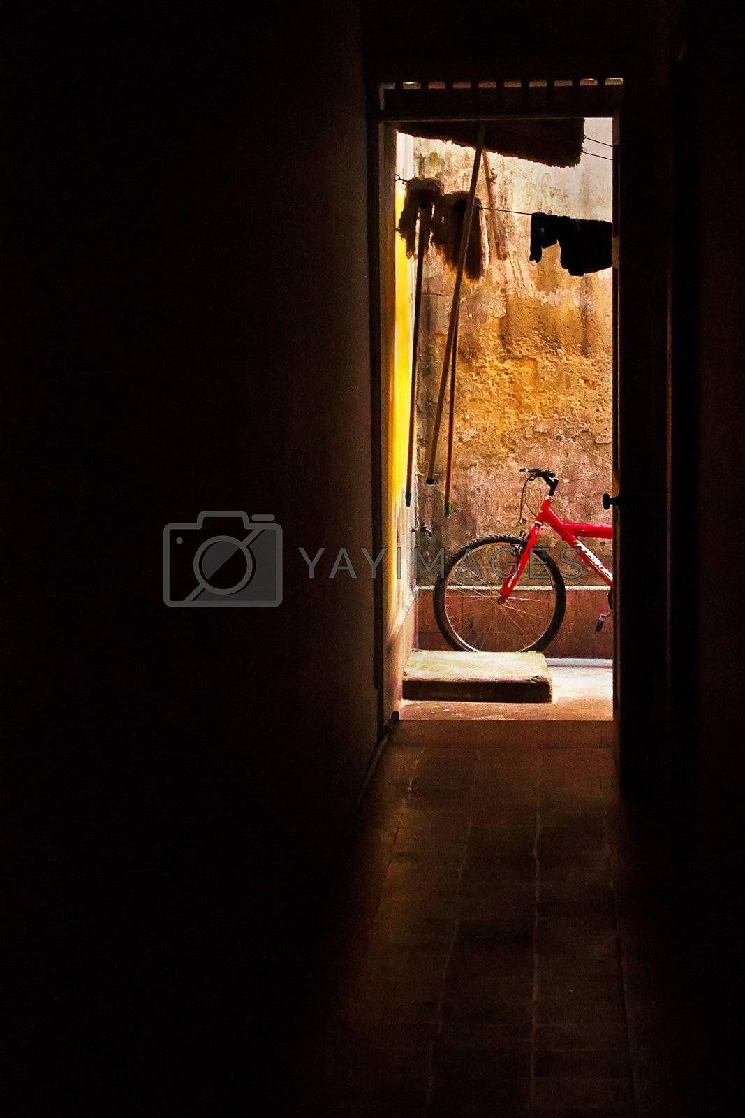 A red bicycle at the end of a hall next to a yellow wall.