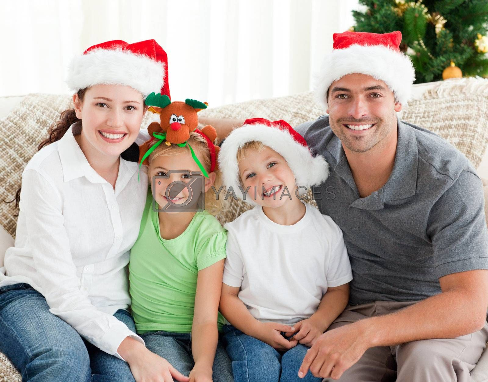 Portrait of a happy family with Christmas hats sitting on the sofa in the living-room