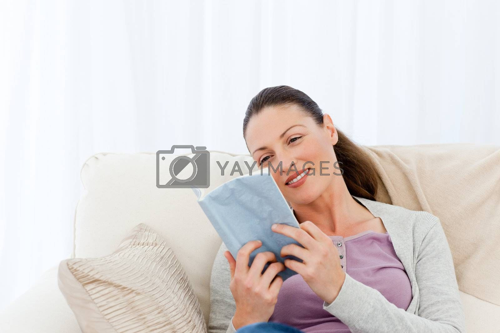 Lovely woman reading a romance sitting on the sofa at home