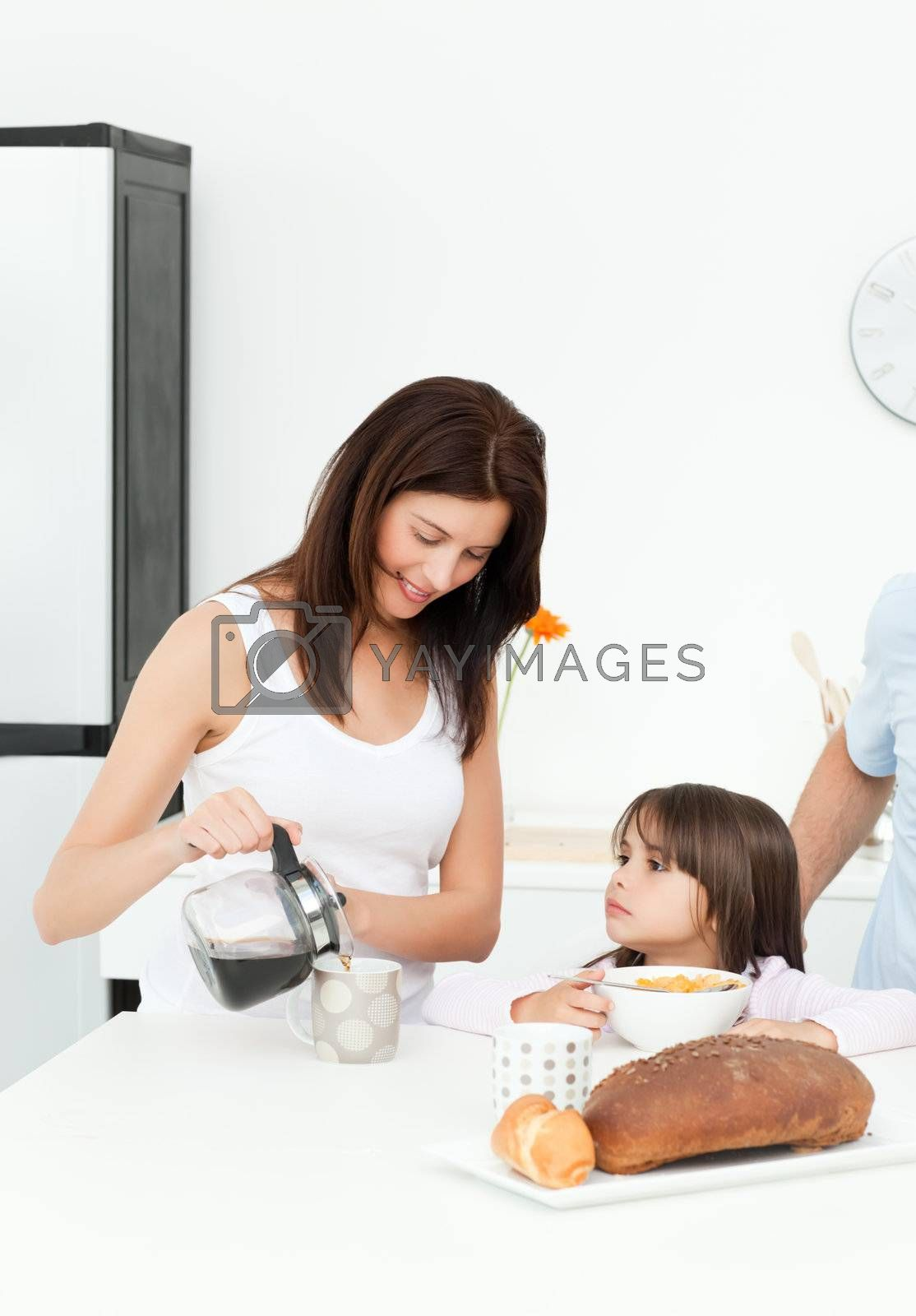 Mother and daughter having breakfast with their family by Wavebreakmedia