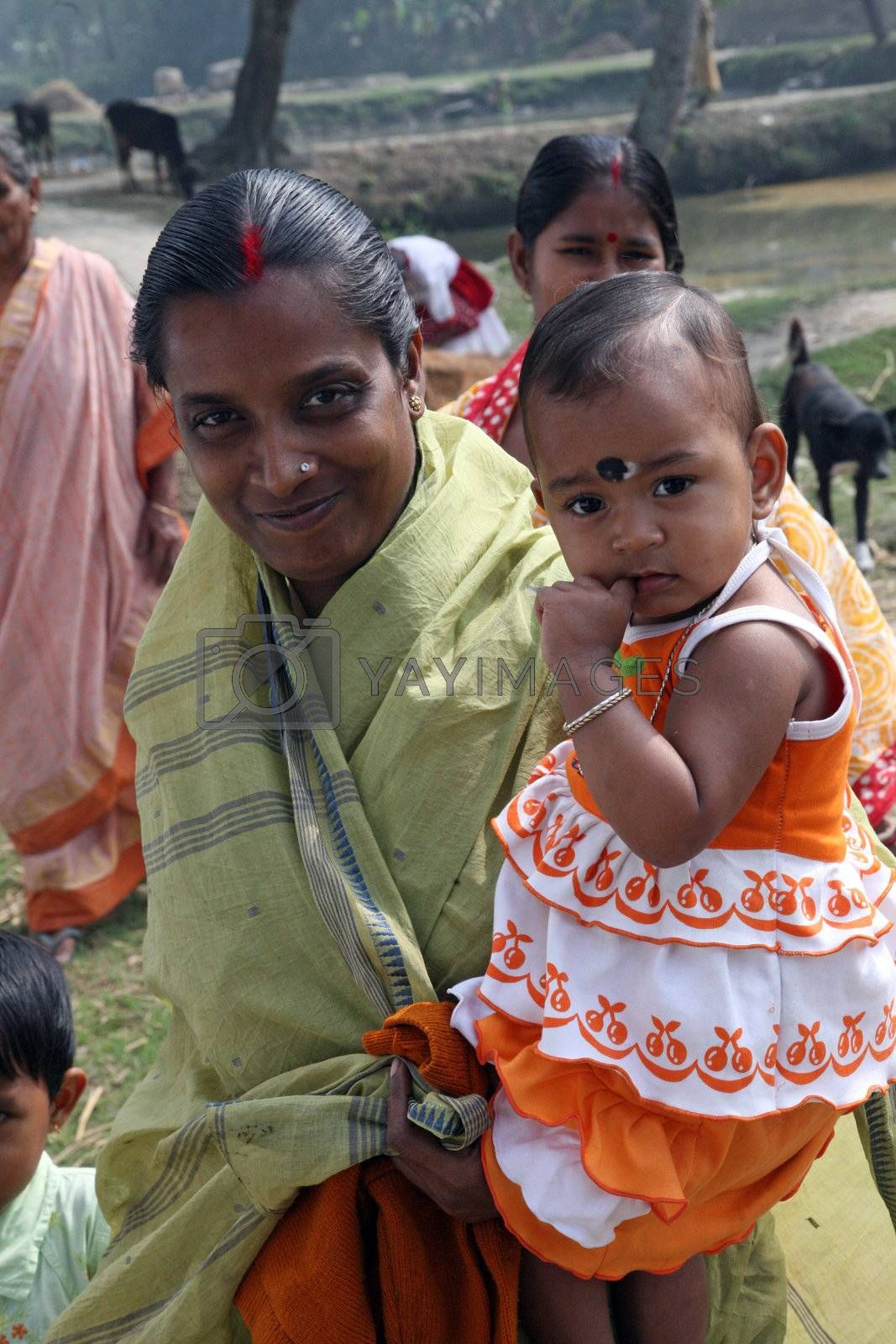 SUNDARBANDS, WEST BENGAL, INDIA - JANUARY 14: mother carries the little girl Sabita Bisvas, 2, to Mass in the village with the Christian majority in Sundarbans, West Bengal, India on January 14, 2009.