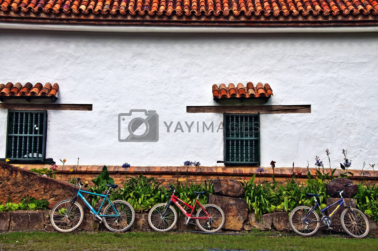 Three bicycles resting against the wall of an old Spanish Monastery.