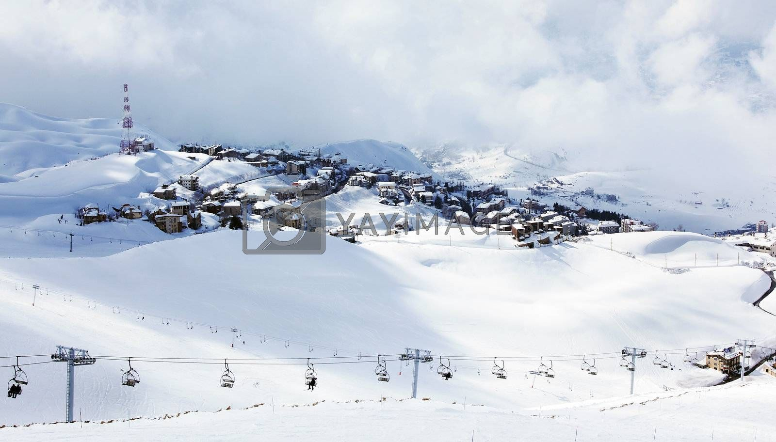 Winter mountain ski resort landscape with snow and cute little houses, chairlift with people playing sport