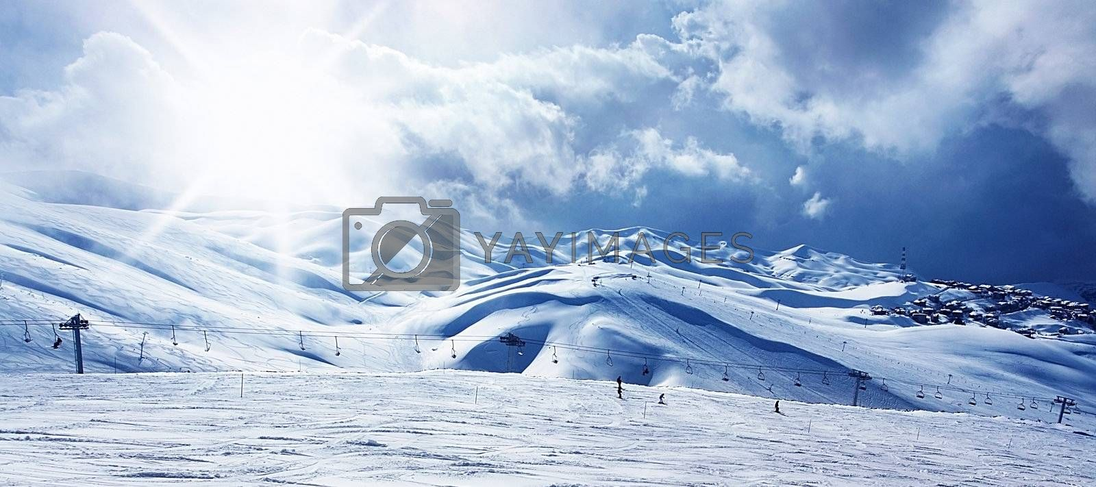 Winter mountain ski resort panoramic landscape with snow, sunny sky and chairlift