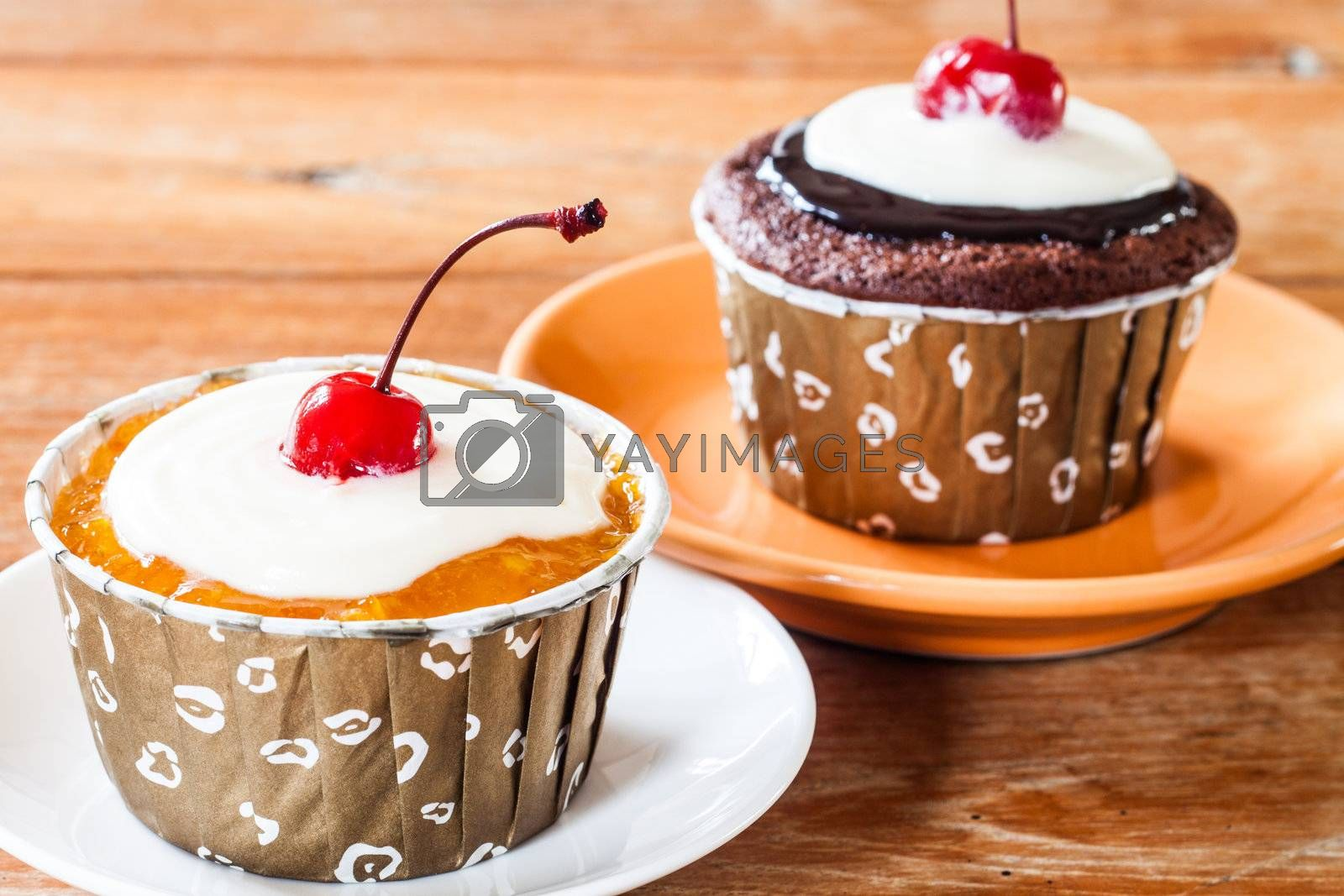 Chocolate and Butter Marmalade Cupcakes decorated with red cherry