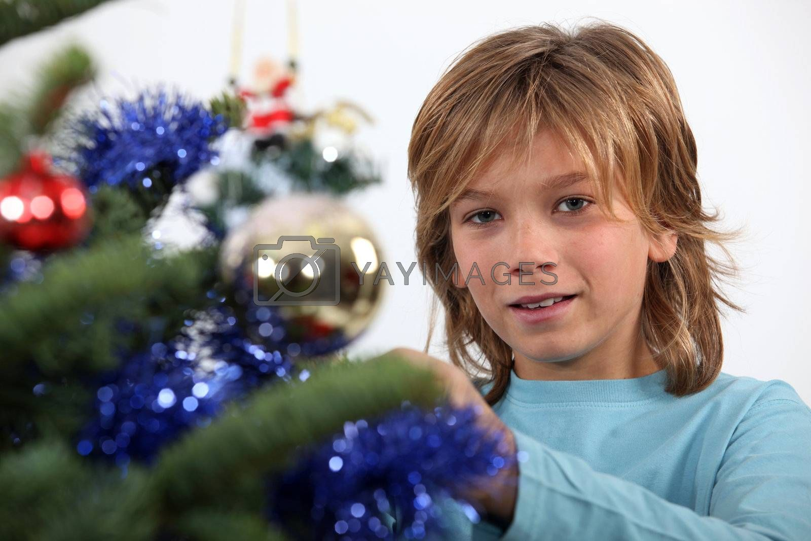 Prepubescent boy decorating a Christmas tree
