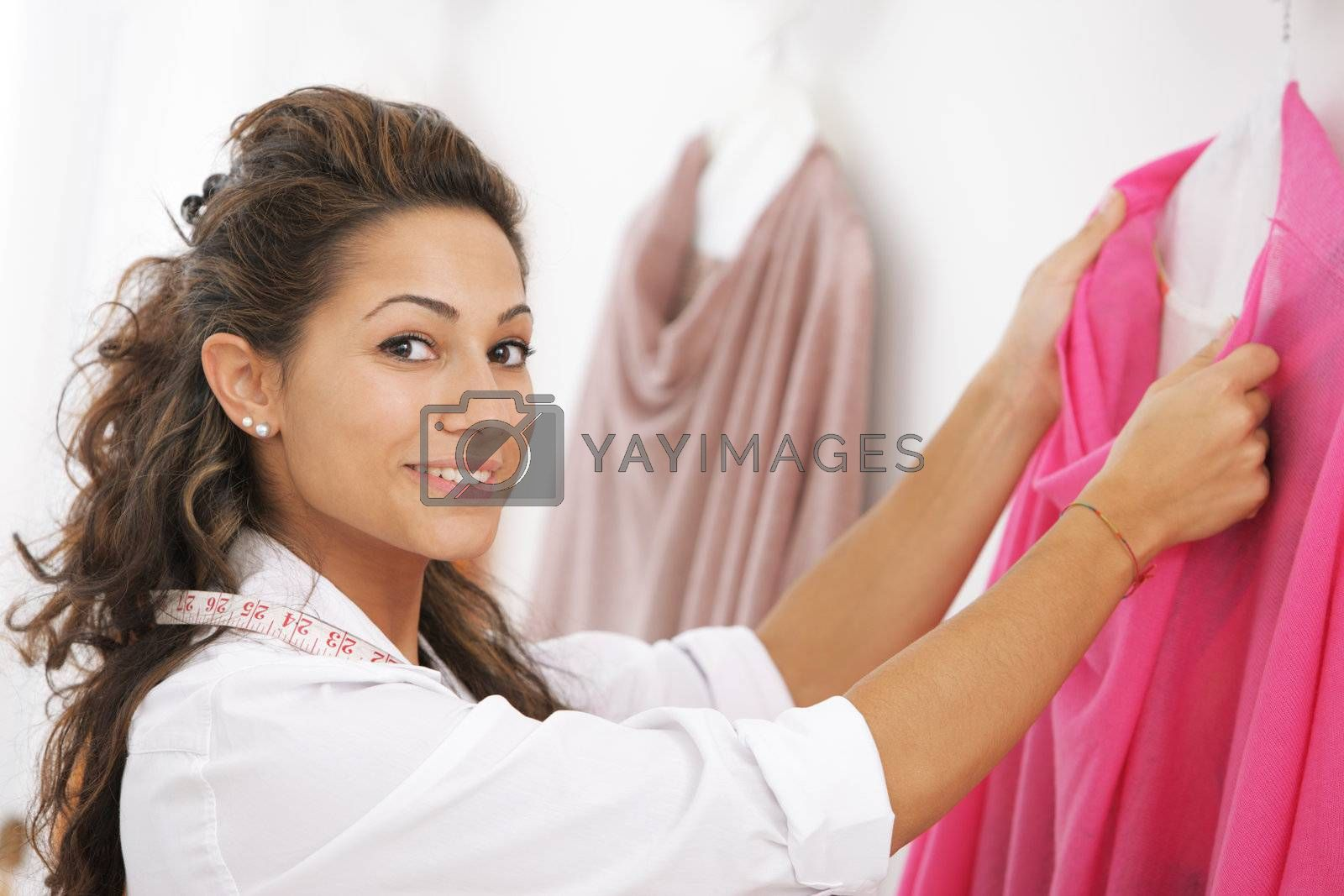Young woman tailor working on dress