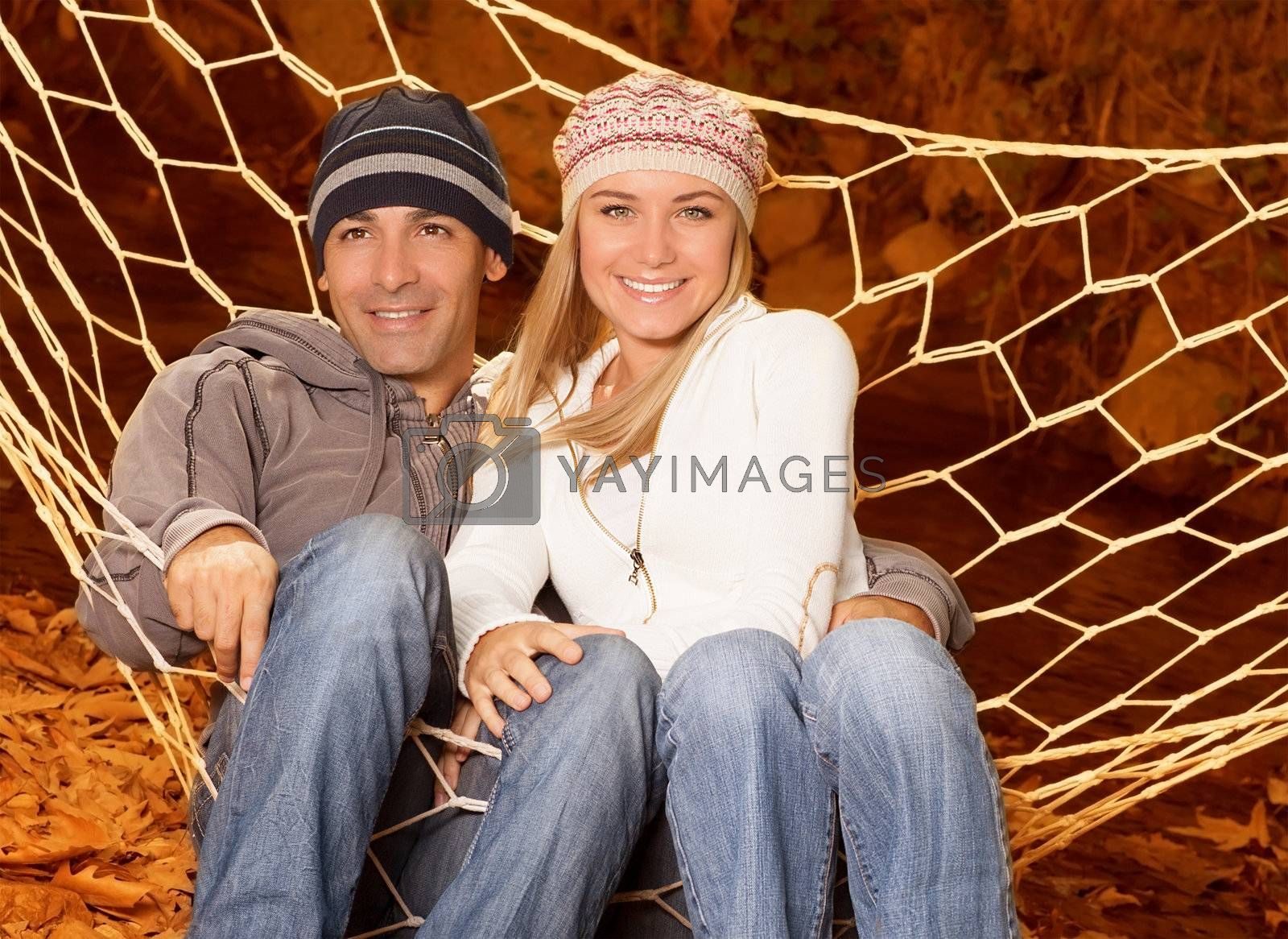 Picture of two loving person swinging in hammock in autumnal park, cheerful pair having fun in fall forest, romantic relationship, young family sitting in hammock on orange autumn background