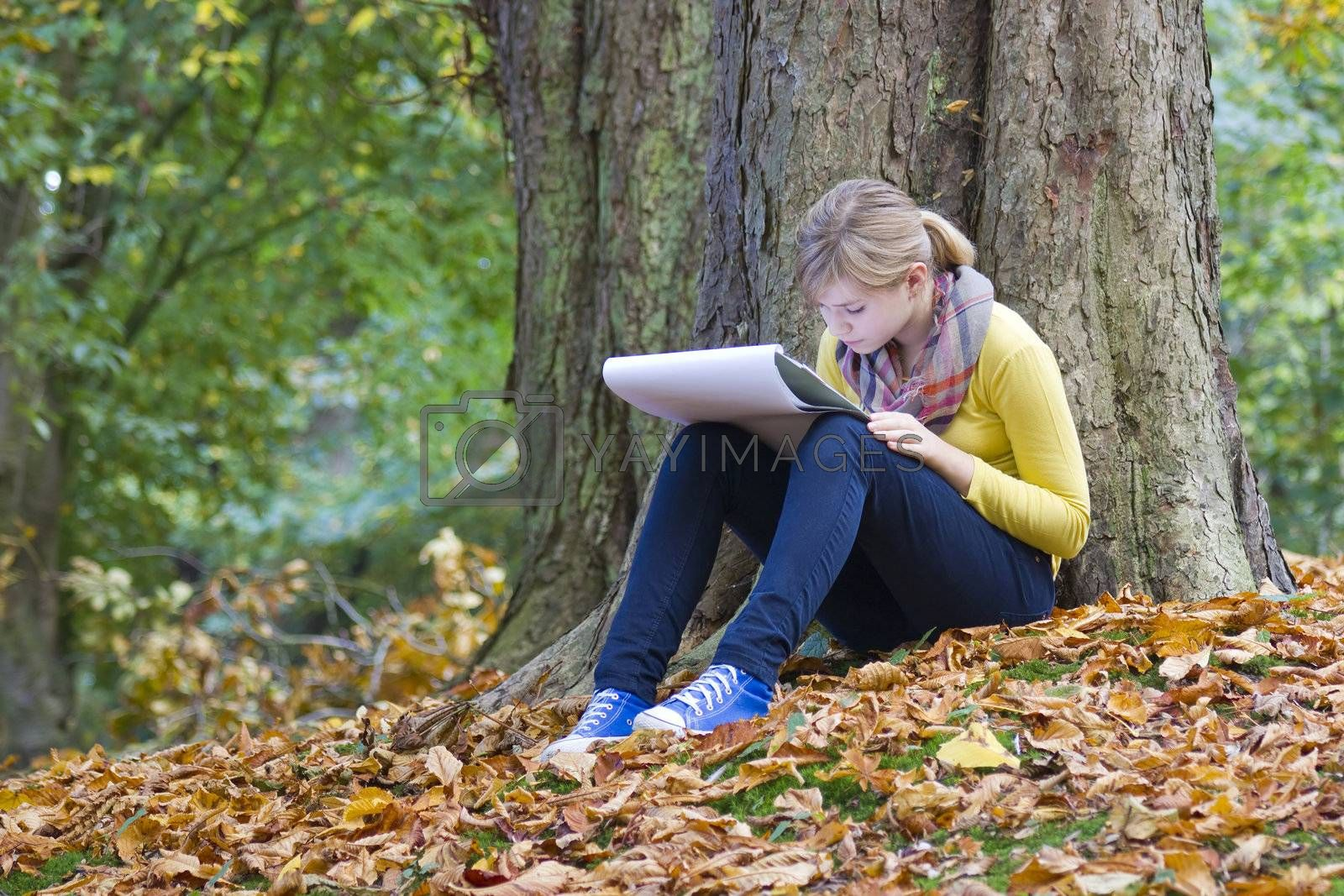 Lovely girl drawing in the park