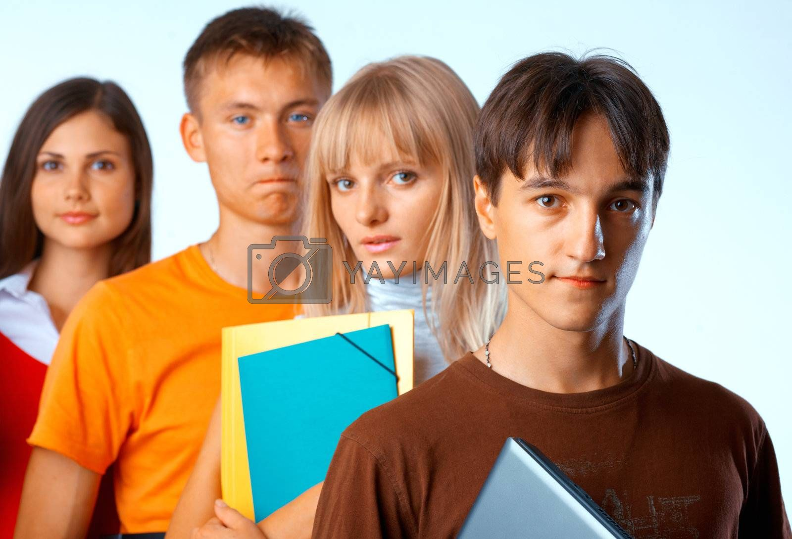 Casual group of college students smiling stand in a row with books on white