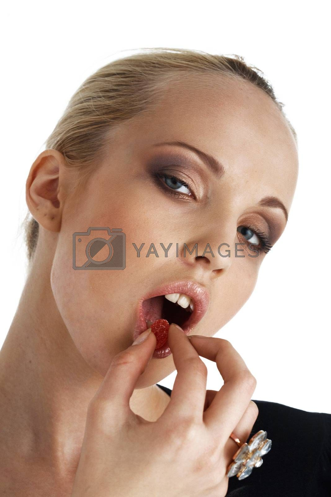 Close-up portrait of young blond model eating a candy over white.