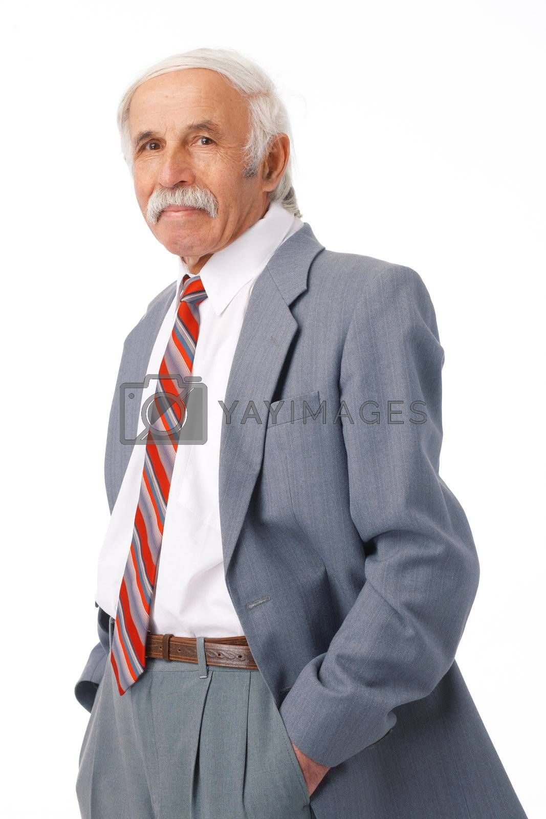 Portrait of an elder man standing with his hands in his pockets.