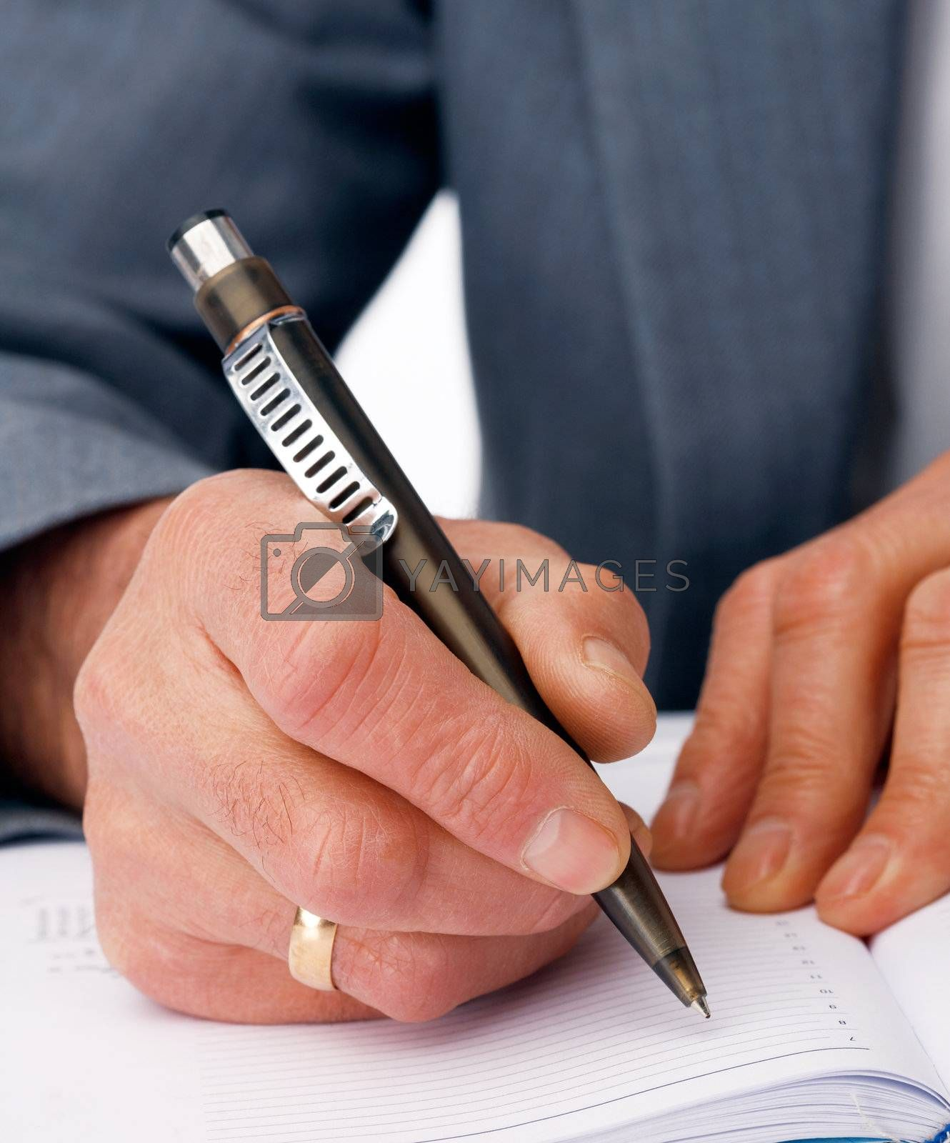 Close-up picture of hands writing in the  business dairy.