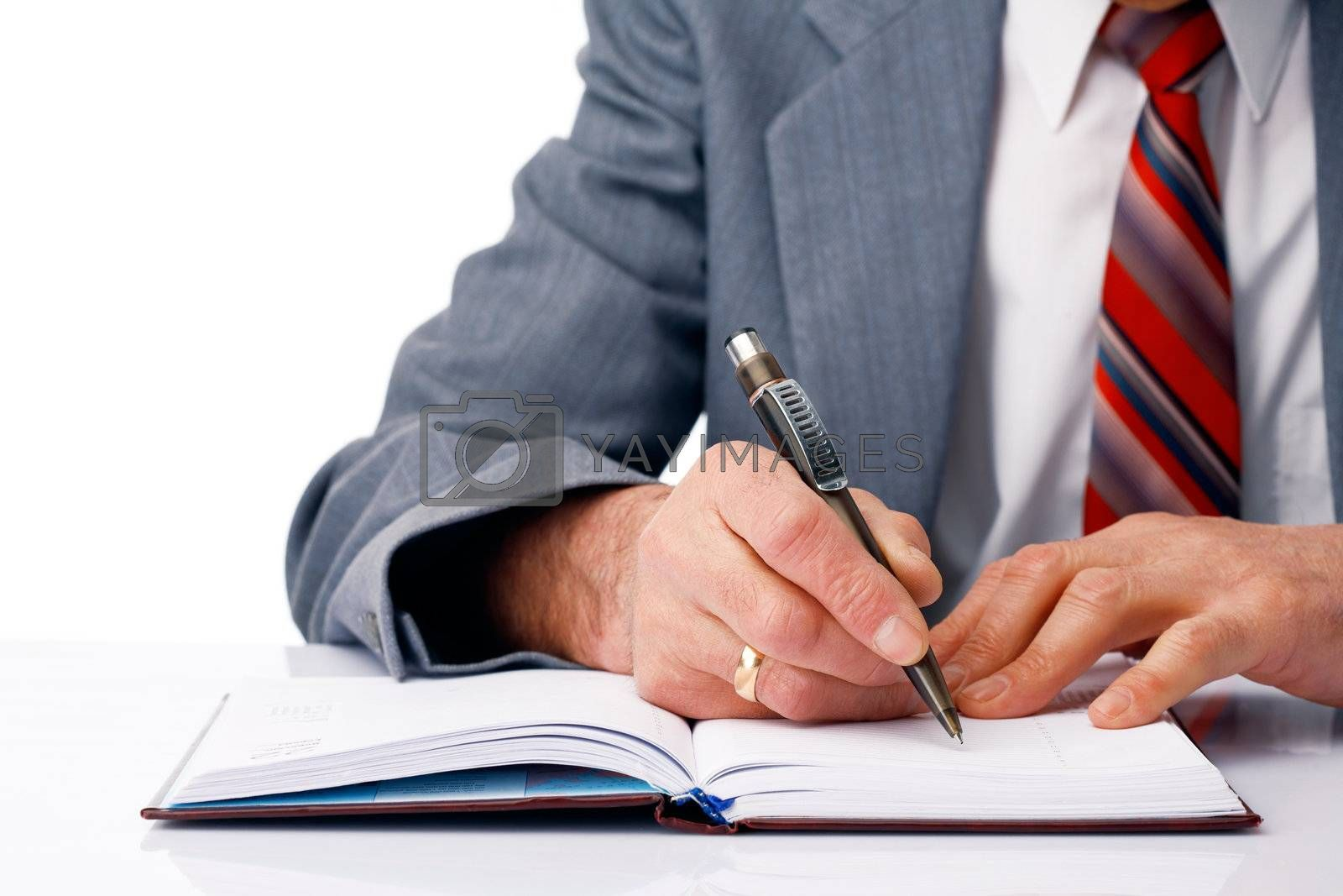 Close-up picture of businessman's hands writing in the dairy.