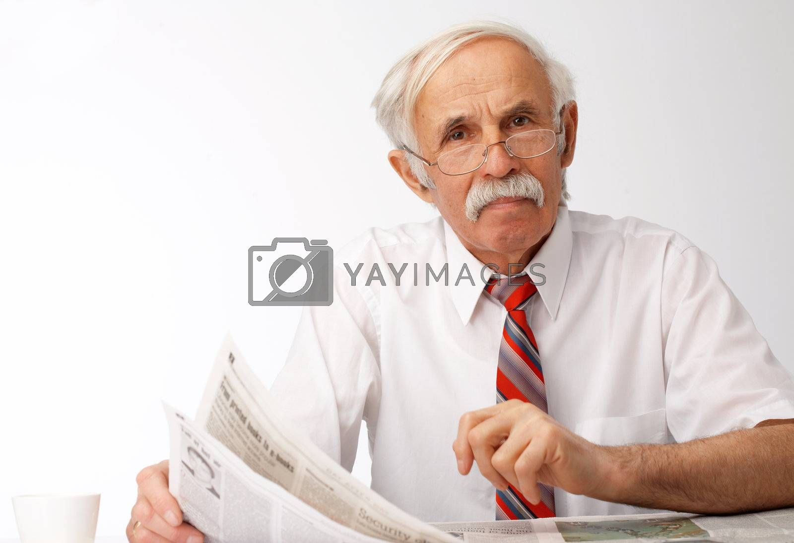 Portrait of an elder man holding an newspaper and looking at you.