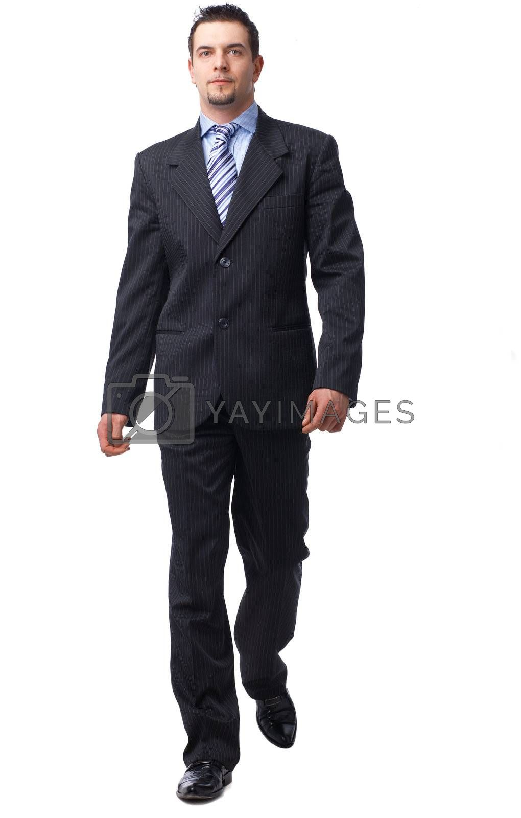 Full length portrait of a confident businessman walking isolated on white.