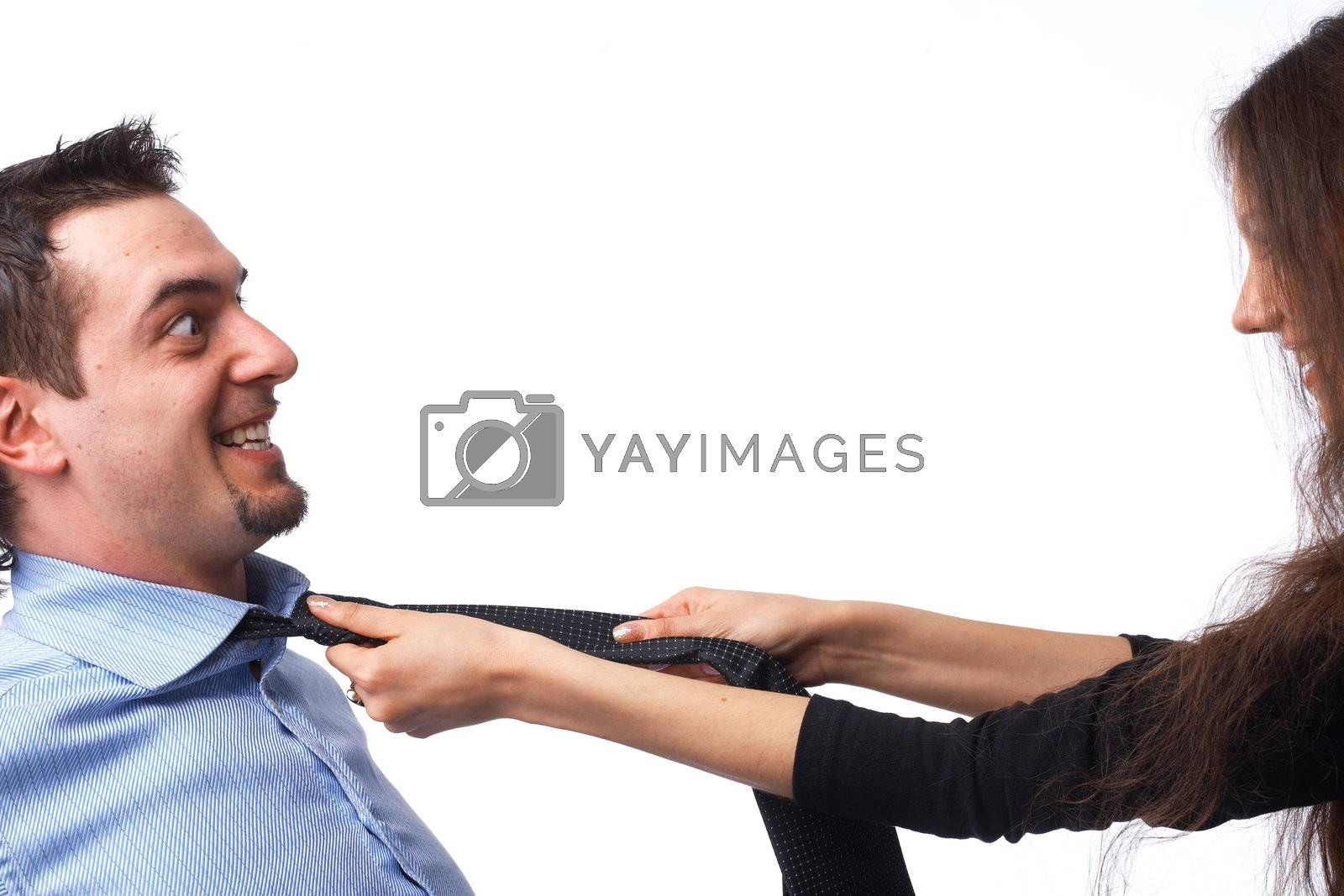 Young couple arguing and struggling, holding the necktie over white.