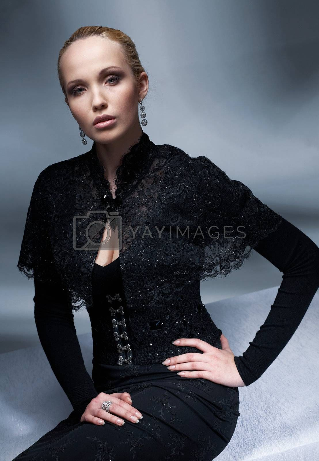 Beautiful blond model sitting and posing in the black vintage clothes.